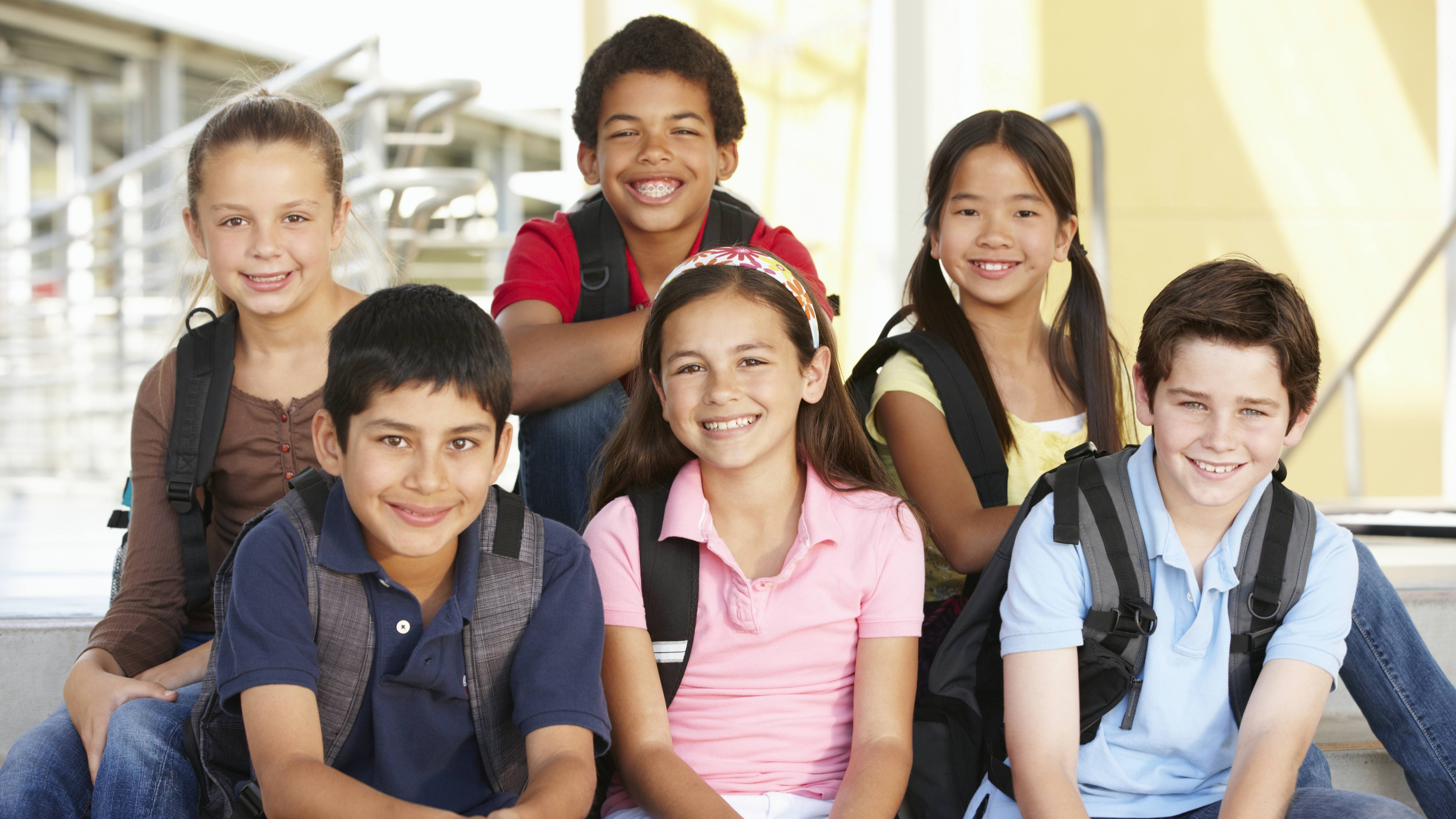 young school children smiling and wearing backpacks, sitting on stairs together