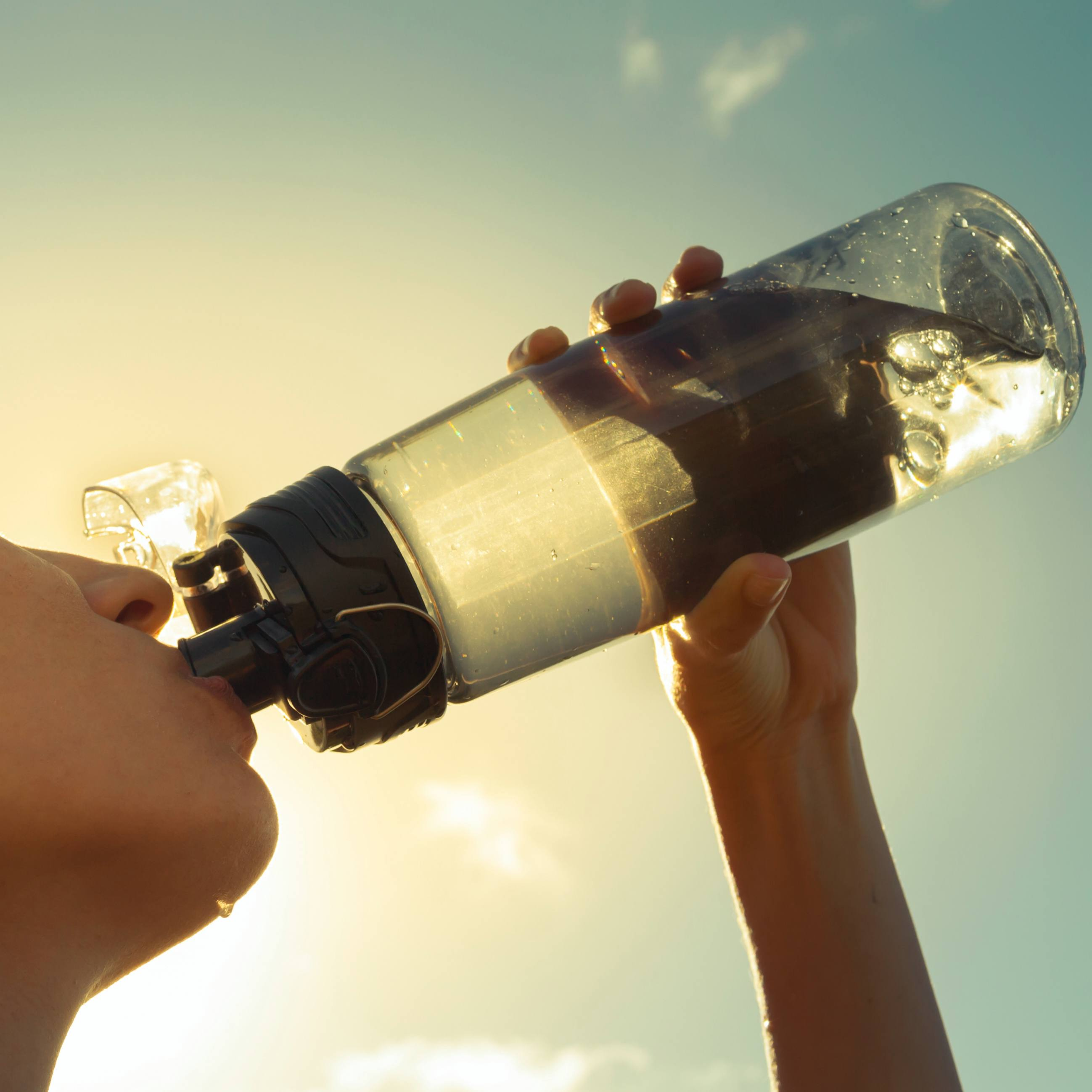 a woman drinking from a water bottle out in the hot sun