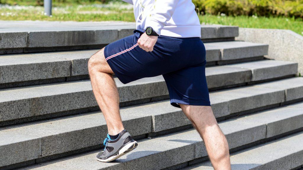 un hombre haciendo ejercicio afuera y corriendo escaleras arriba