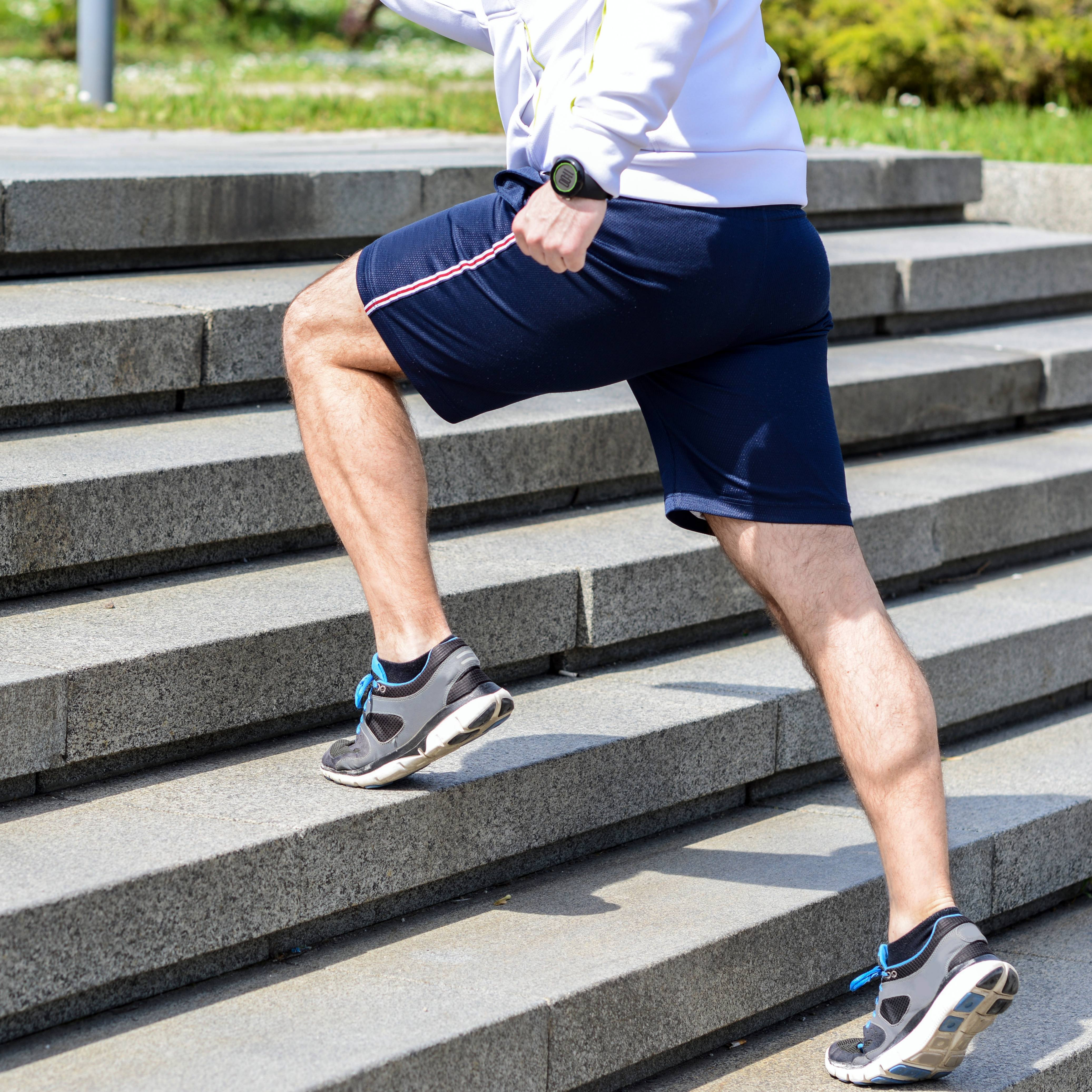 a man exercising outside and running up stairs, perhaps for interval training