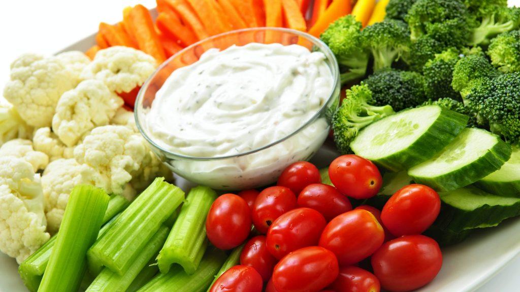 Un plato lleno de verduras frescas, como zanahorias, tomates, pepinos, brócoli y coliflor