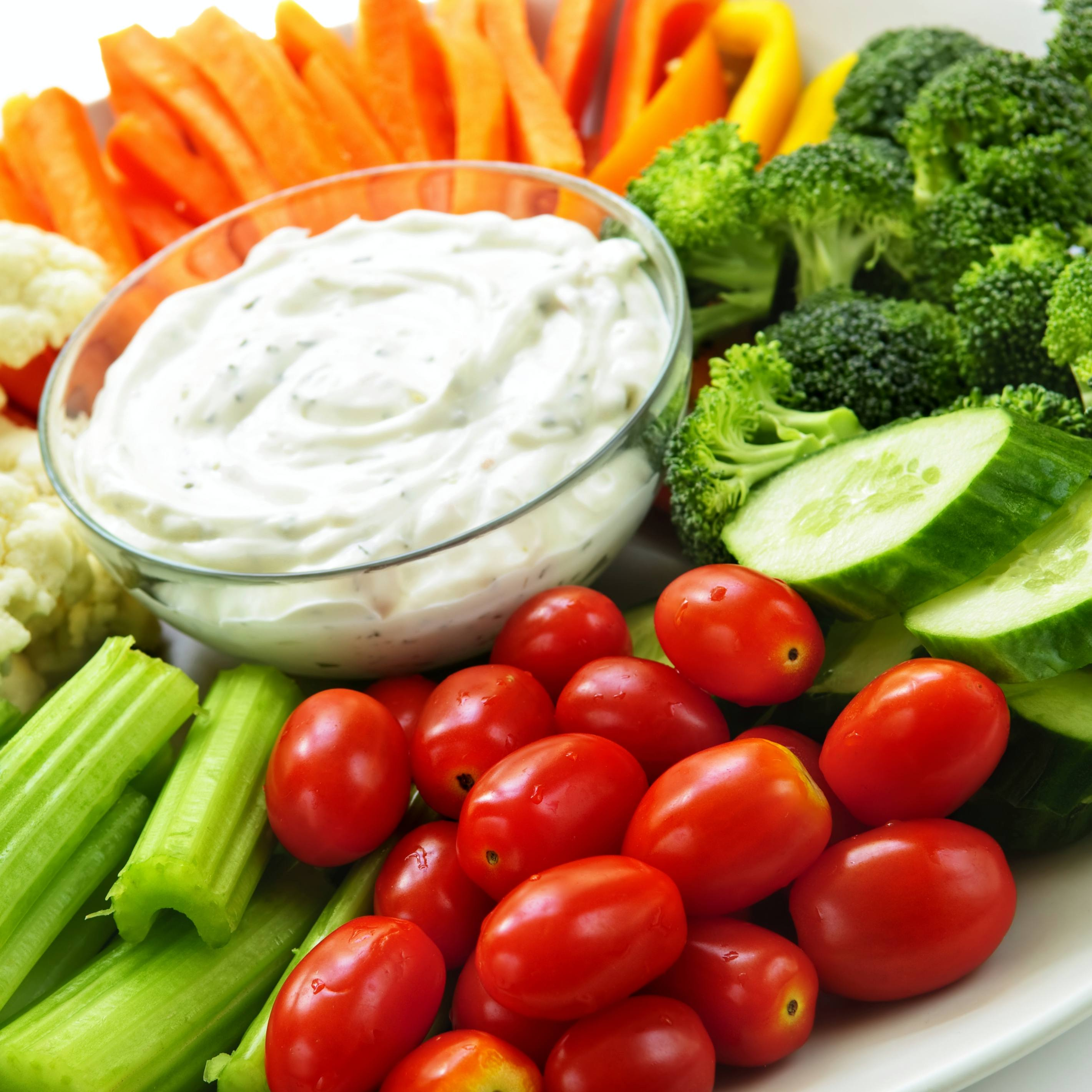 a fresh vegetable platter filled with carrots, tomatoes, cucumbers and more