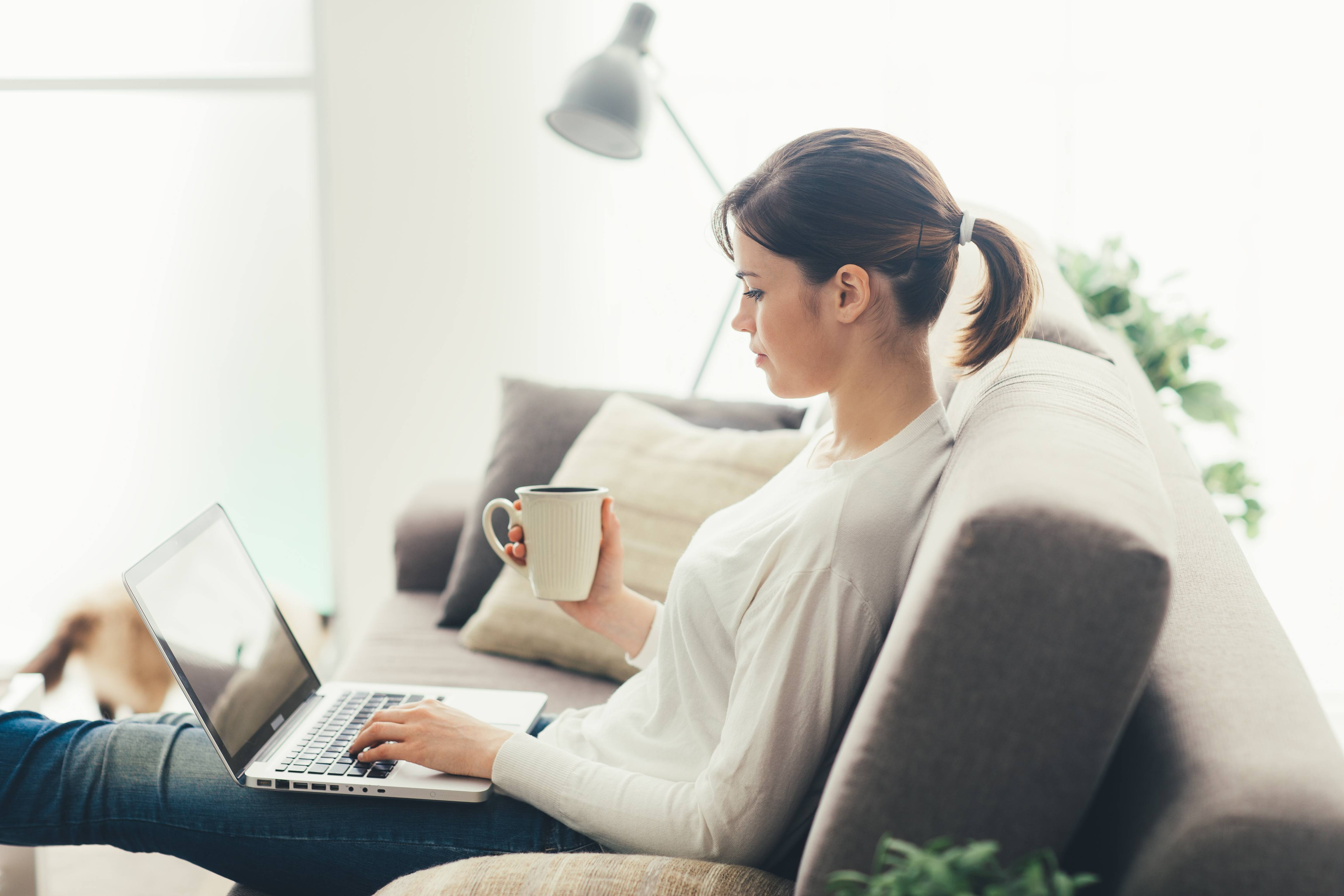 a side view of a young woman sitting on a couch with a cup in her hand, looking at a laptop screen