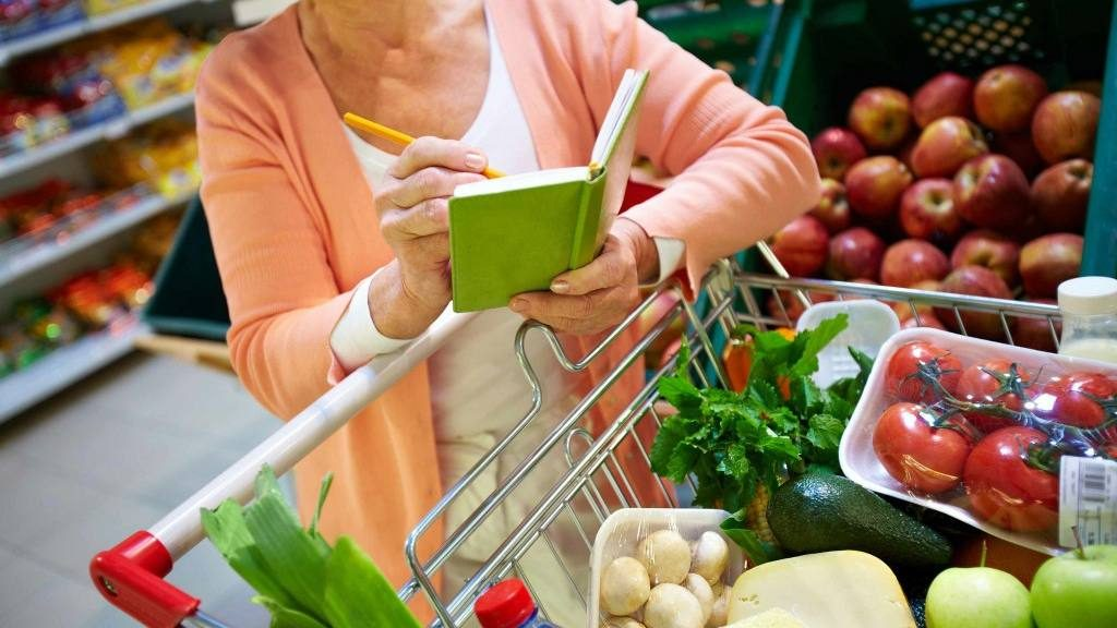 a woman in a grocery store and a cart full of fruits and vegetables, checking her shopping list