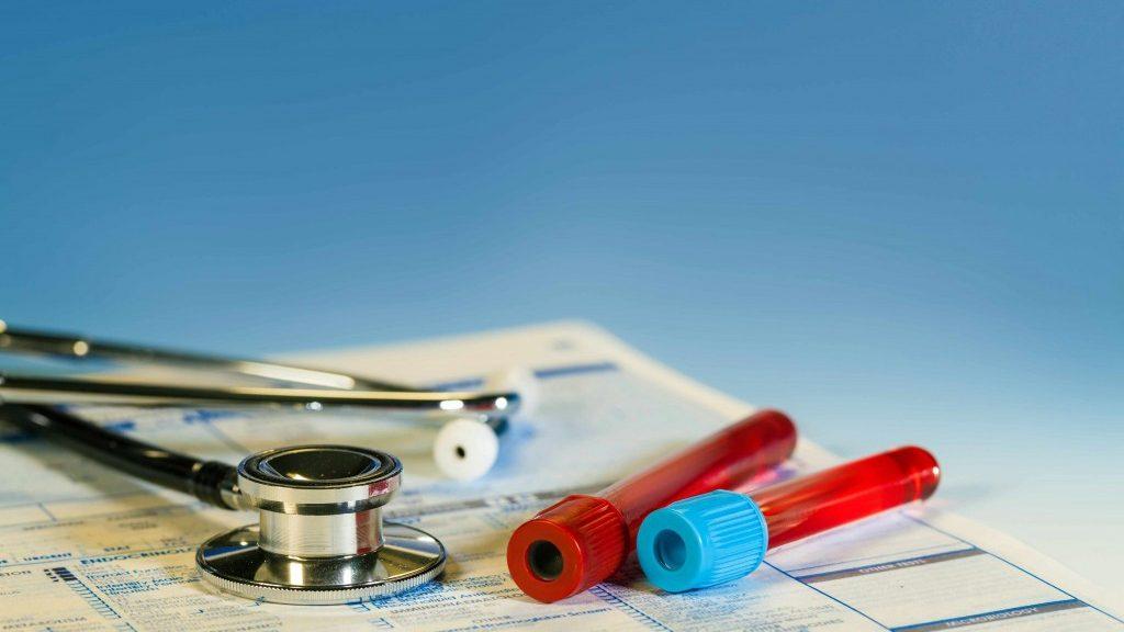 Un estetoscopio y unos tubos de ensayo con sangre descansan sobre un expediente de laboratorio