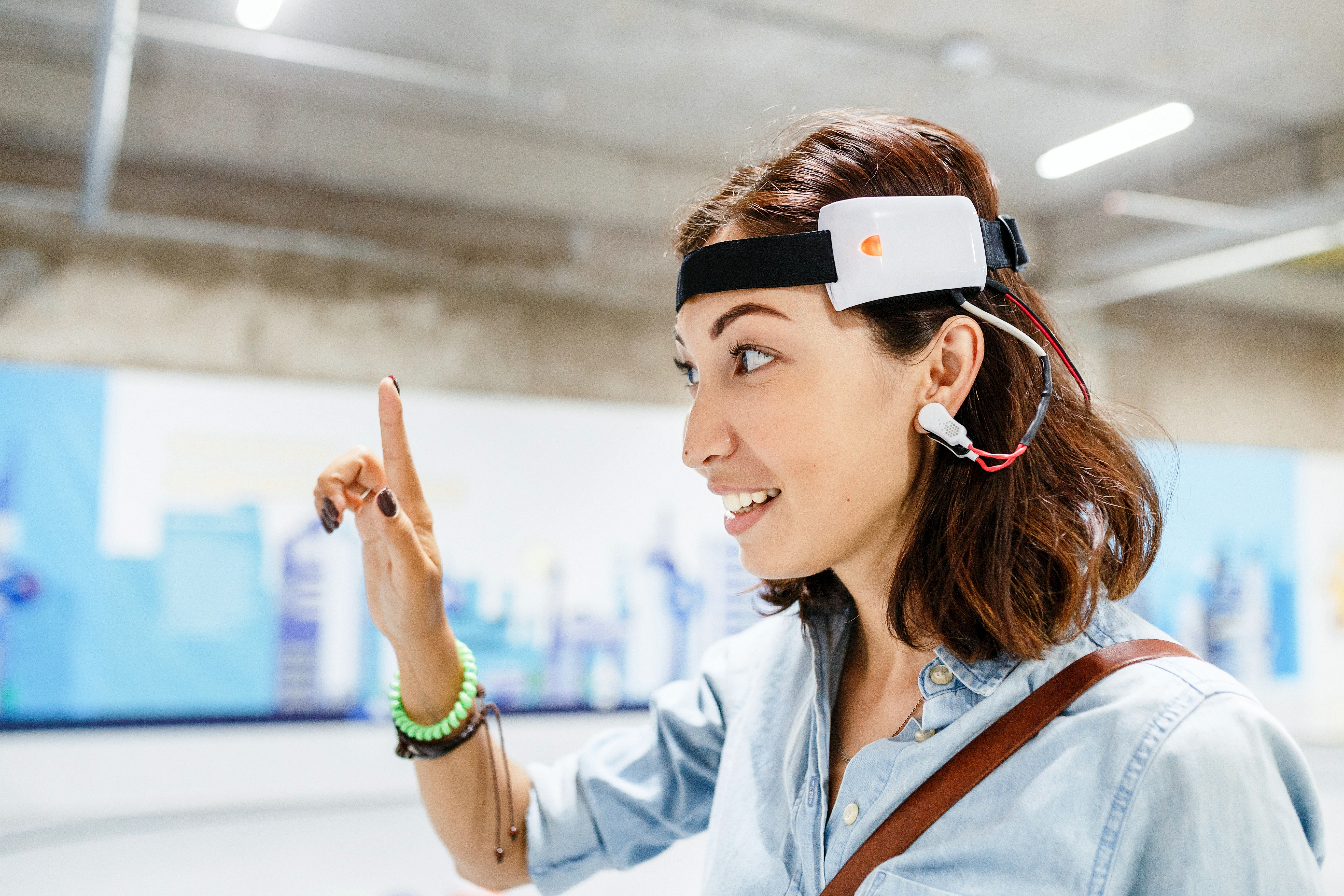 Woman with digital headset sensor connected to her ear, reading brain impulses