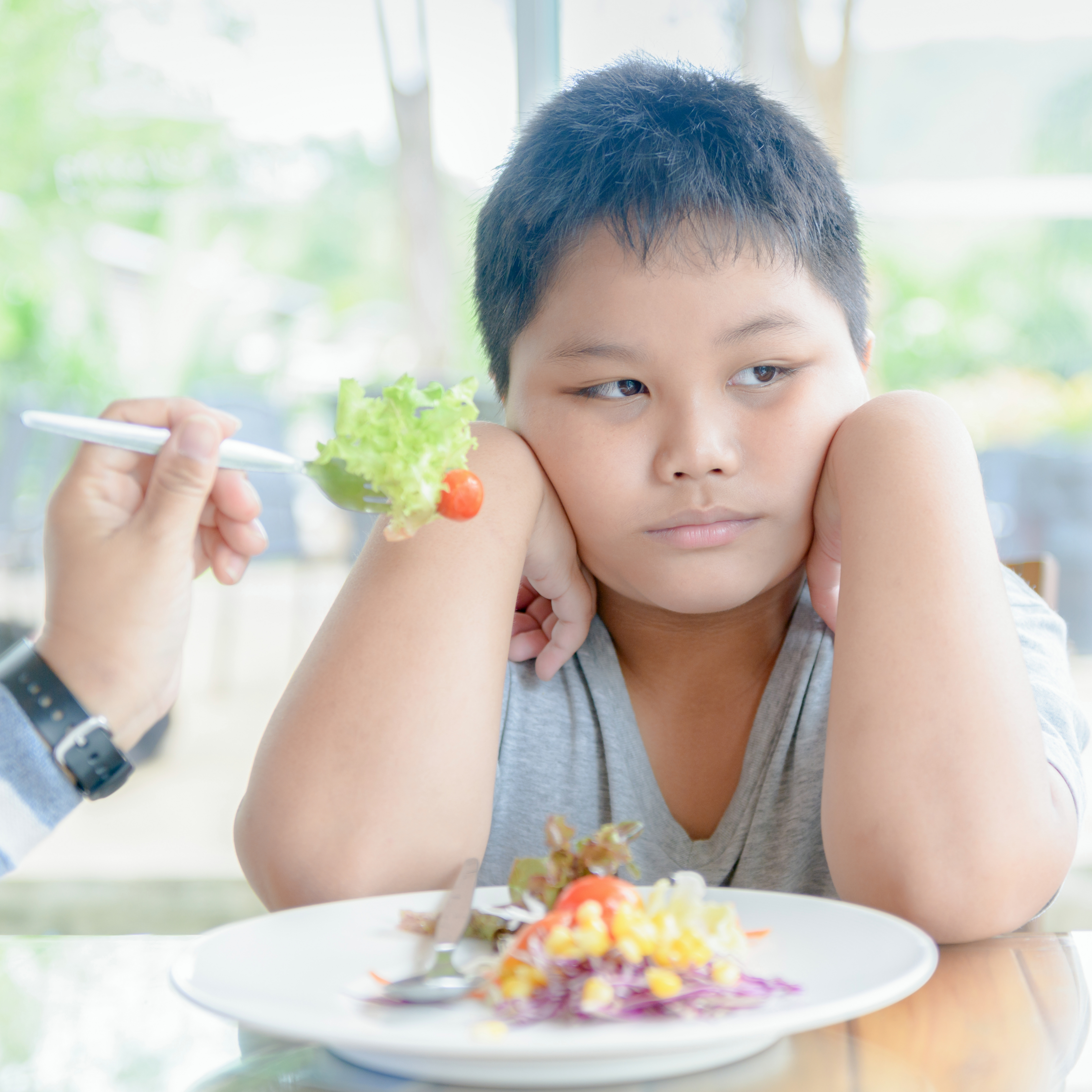 a young boy pouting at a table with someone trying to feed him some vegetables, not interesting in eating