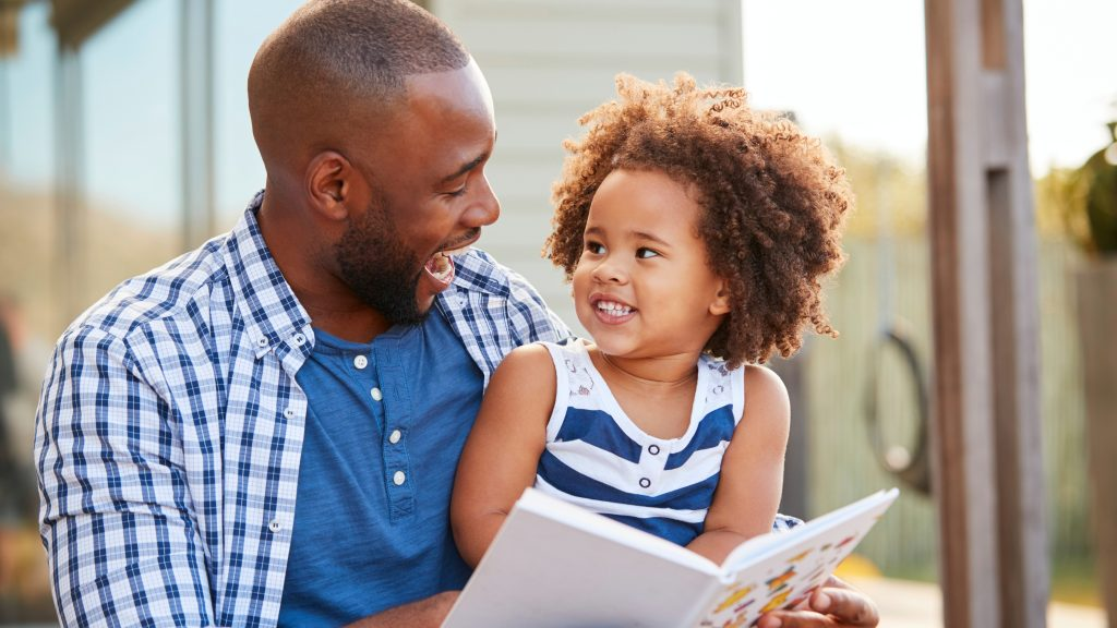 an adult man smiling and reading a book to a happy little girl