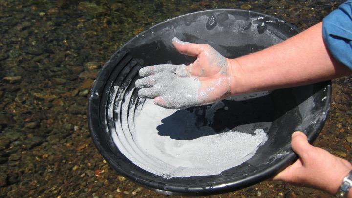 Una persona sostiene un tazón de alfarería cerca de un río con arcilla blanca y tiene en la mano un poco de la arcilla