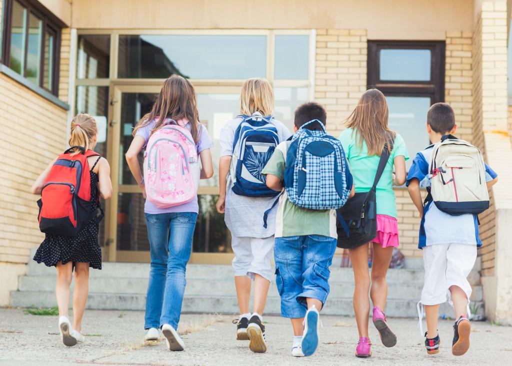 kids walking into school with backpacks