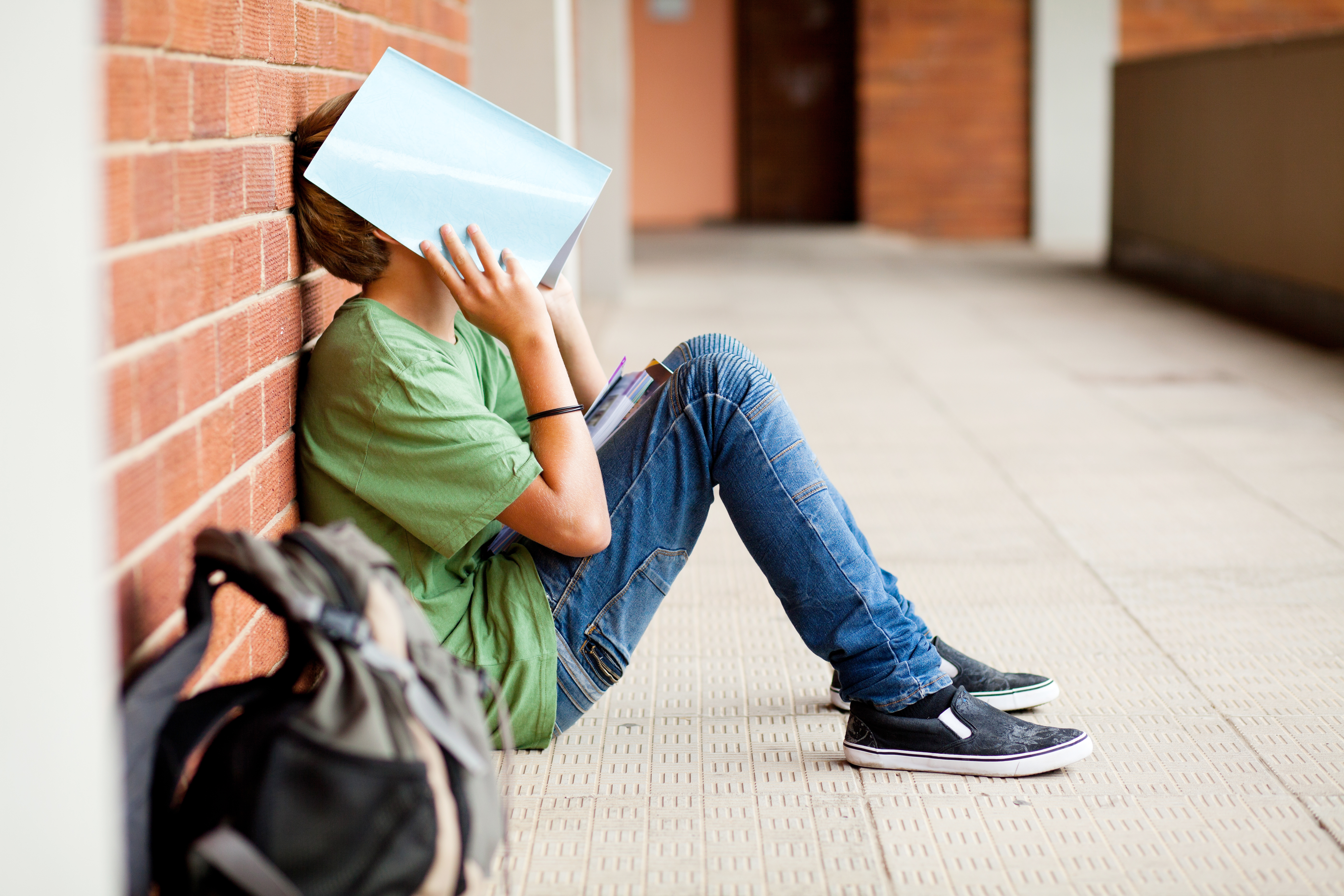 a tired student sitting on the ground using school book to cover his face, maybe stressed, anxious or frustrated