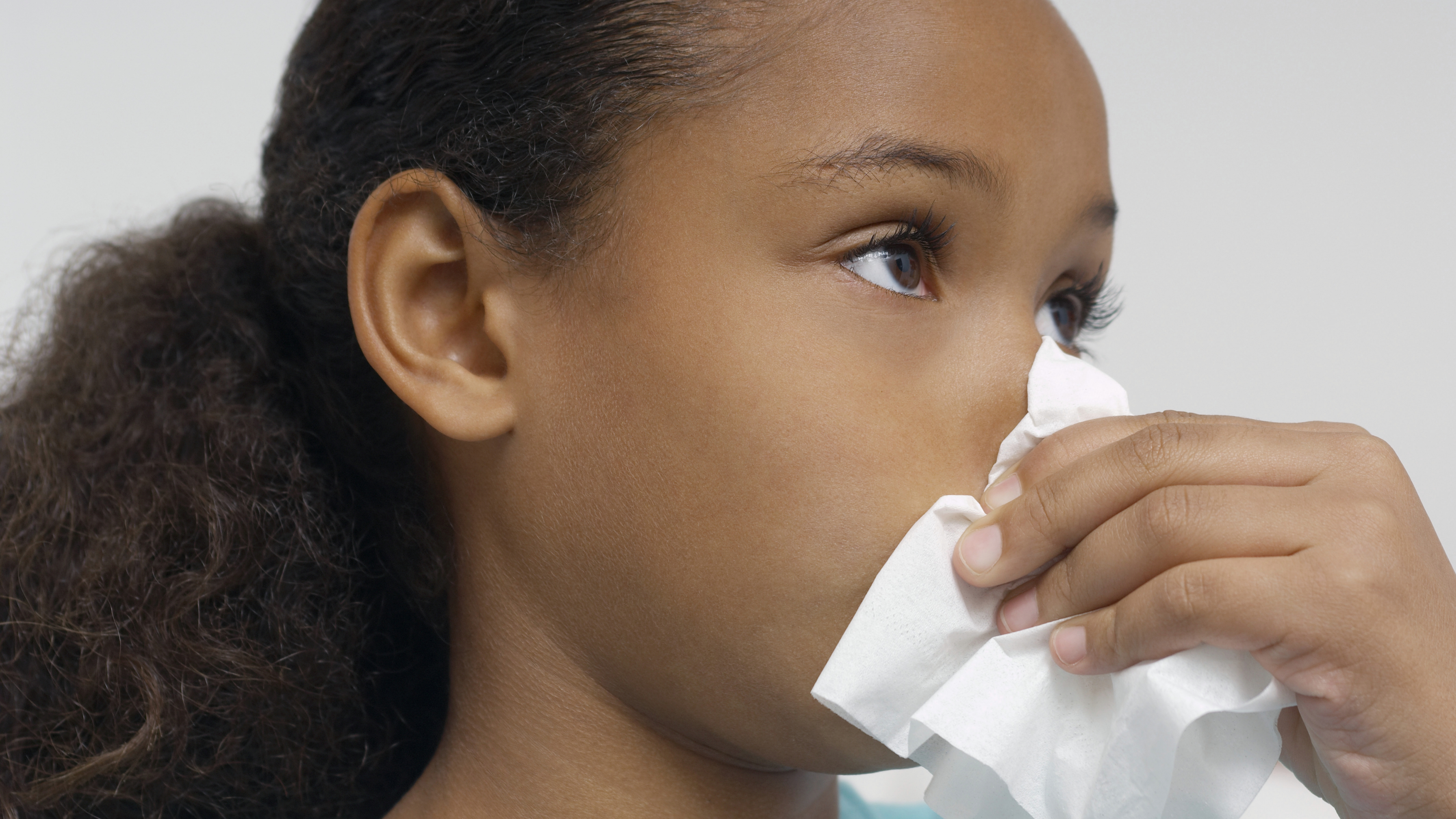 a young girl blowing her nose, perhaps sick with a cold or allergies