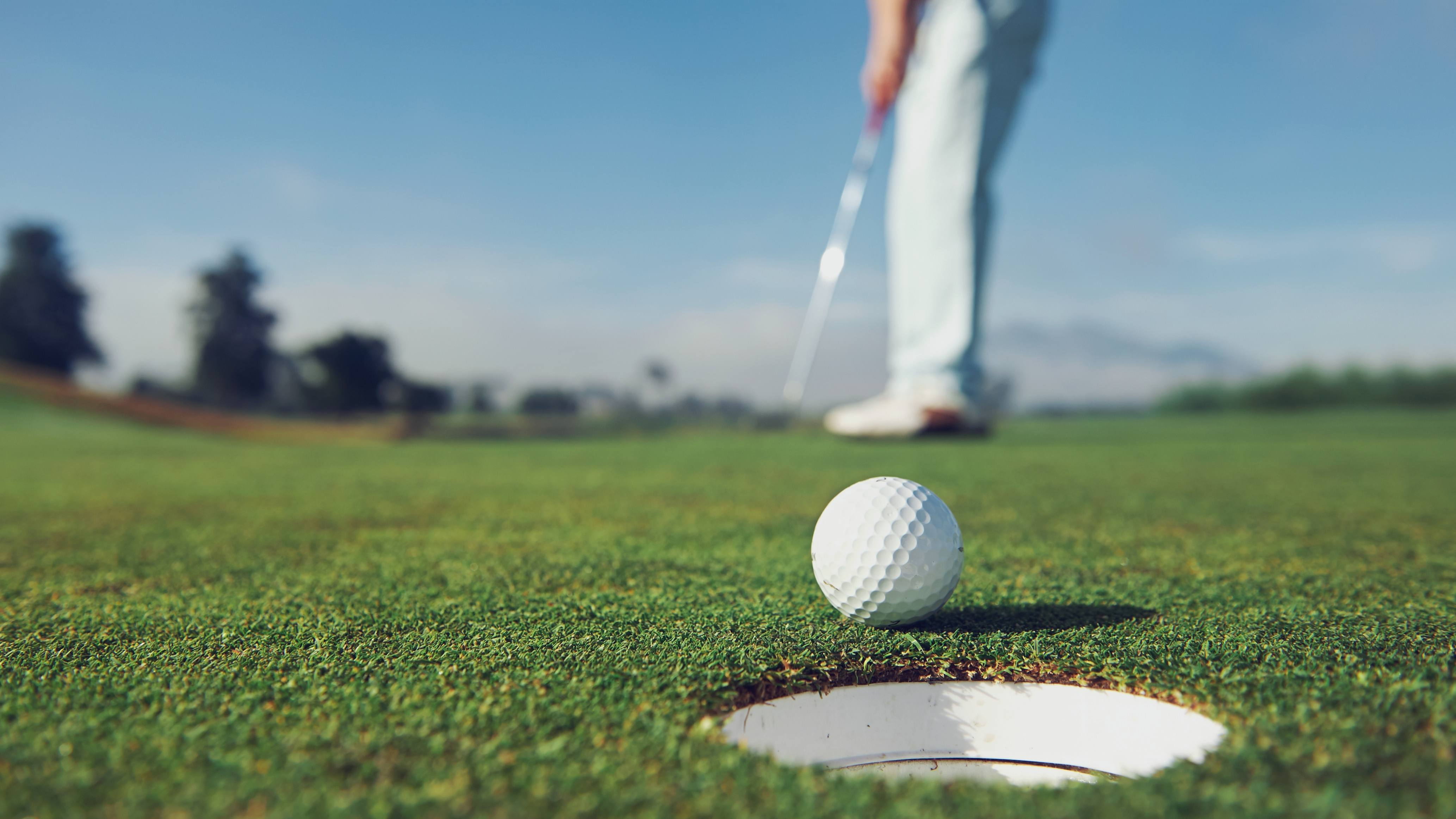close up of a man hitting a golf ball, putting it in the hole