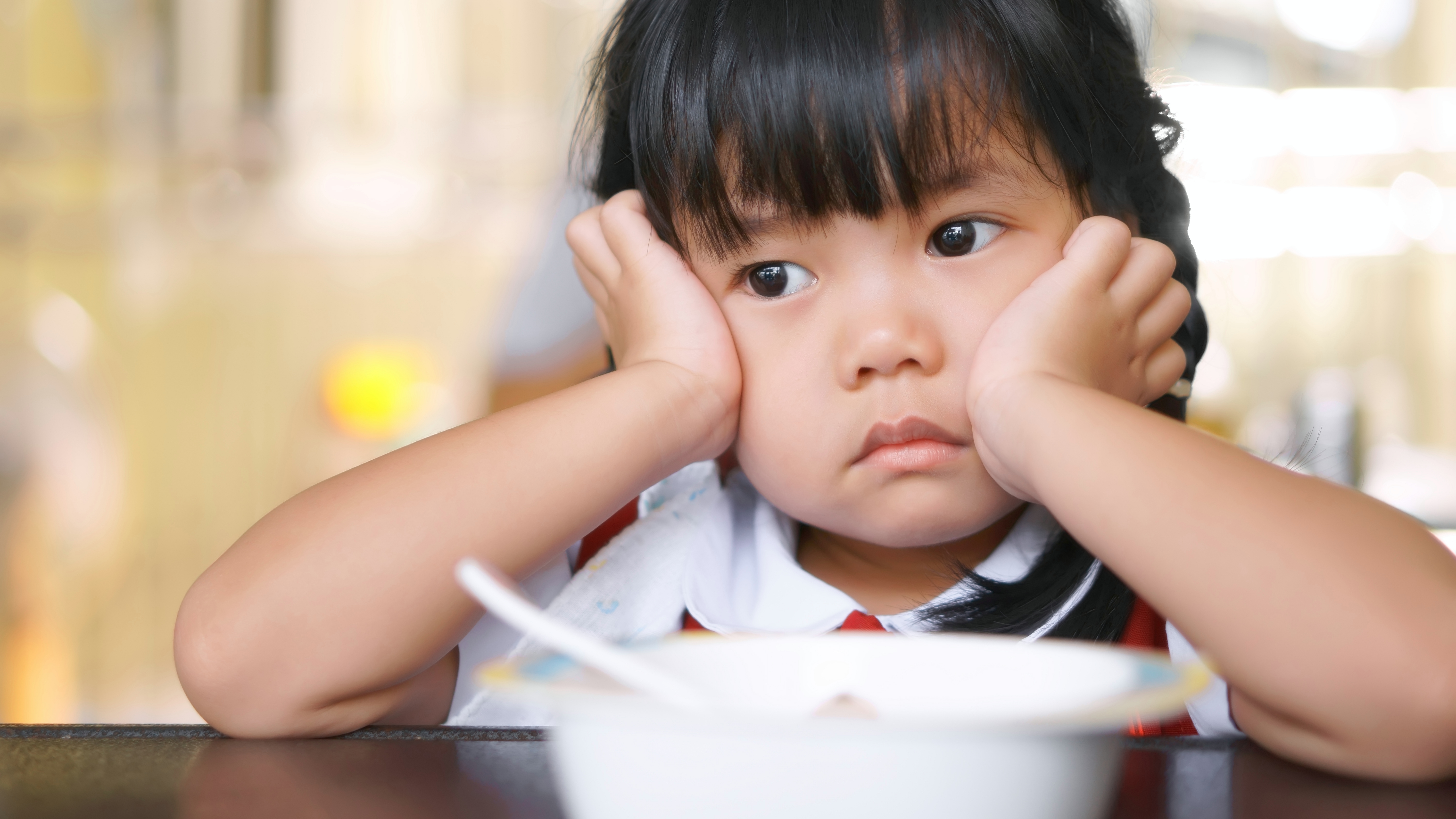 a little girl looking sad and pouting with her head on her hands and a food bowl in front of her, looking like a picky eater