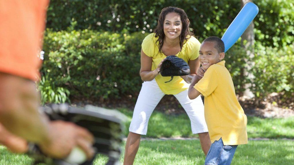 a family playing baseball or whiffle ball outside