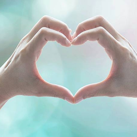 closeup of two hands forming the shape of a heart