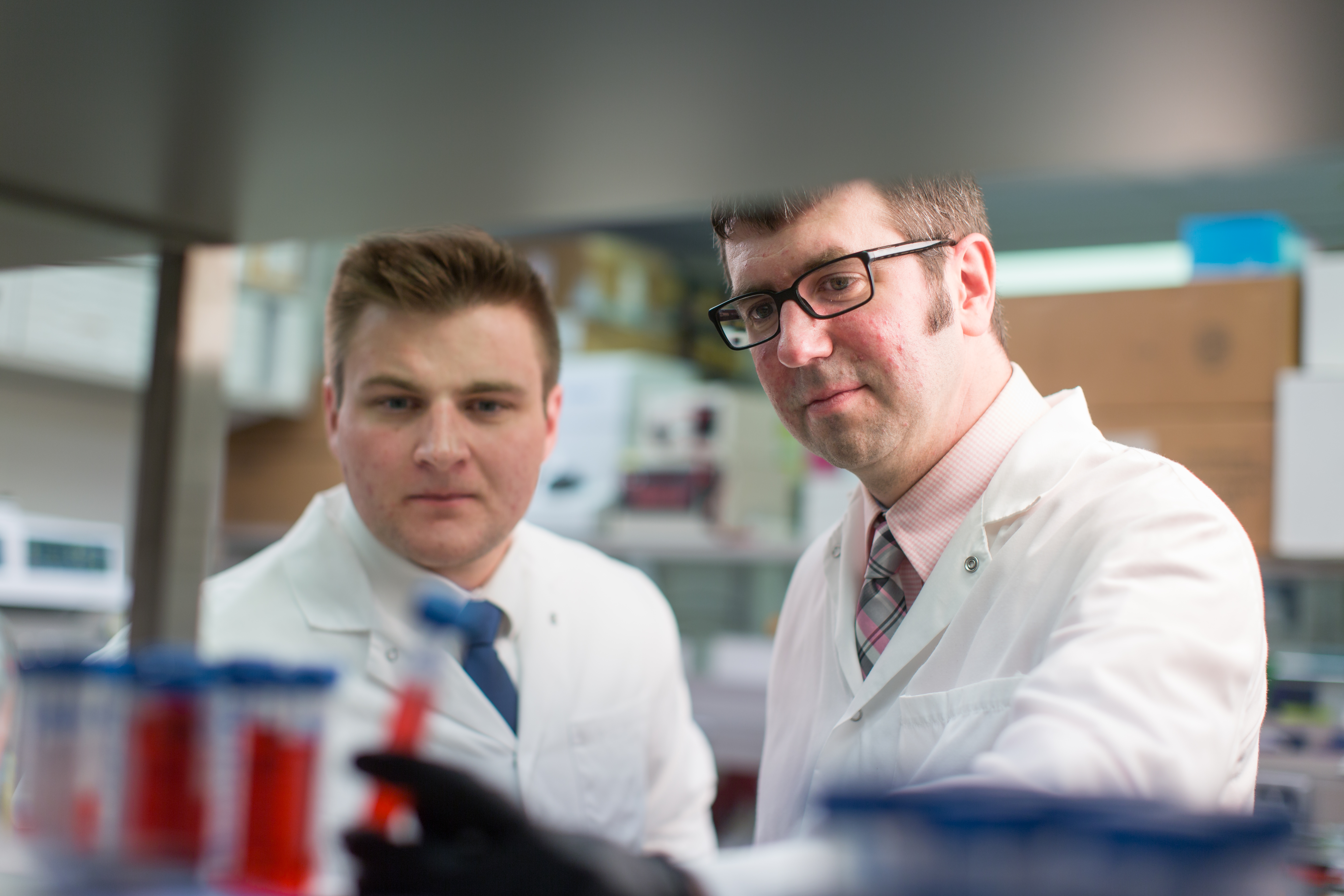 Tyler Bussian and Darren Baker, Ph.D., looking at sample tubes