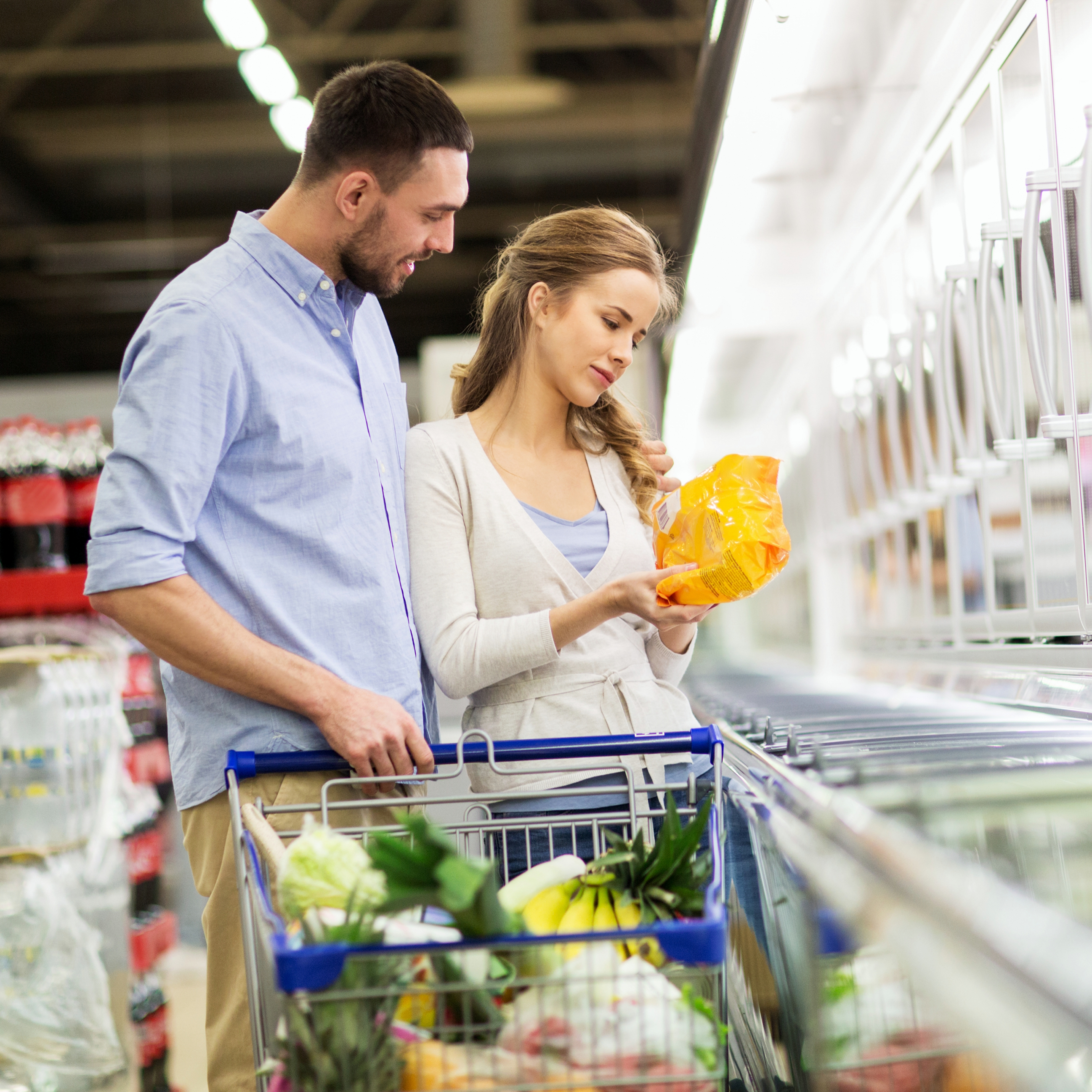 a young couple in a grocery store with a shopping cart and looking at items