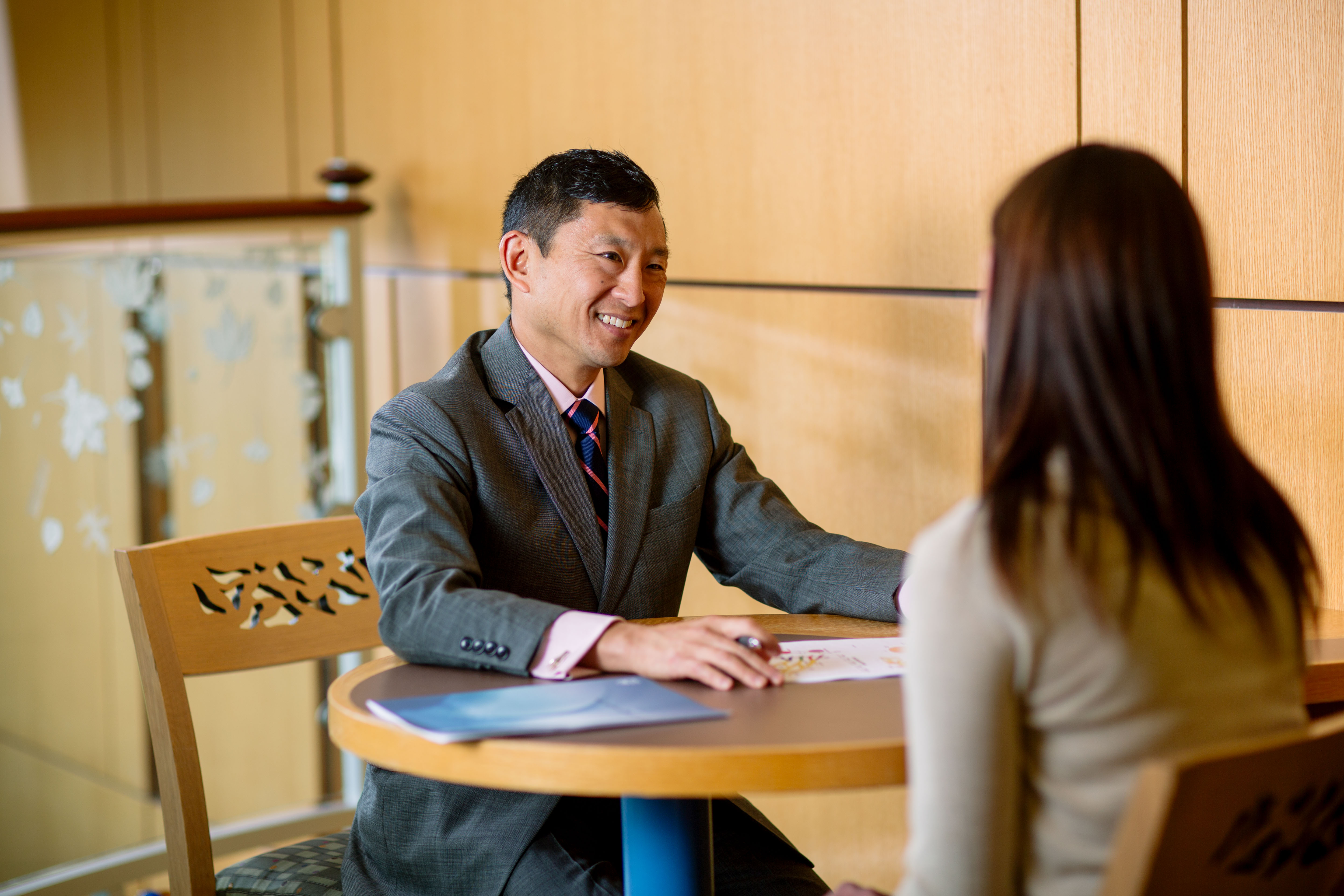 smiling physician talking with a patient at table