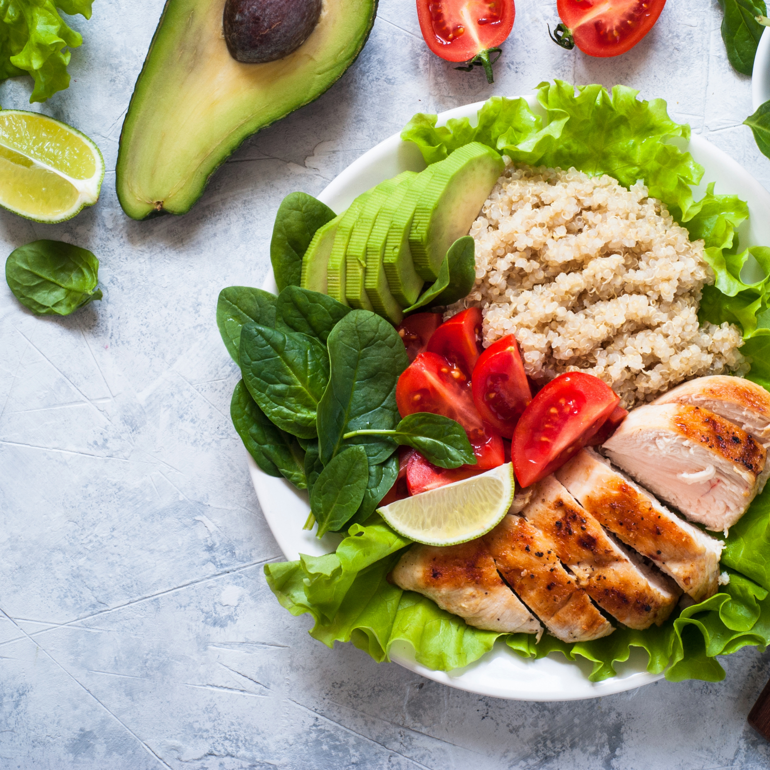 Balanced meal: fresh salad with quinoa, chicken breast, avocado, spinach, lettuce and tomatoes