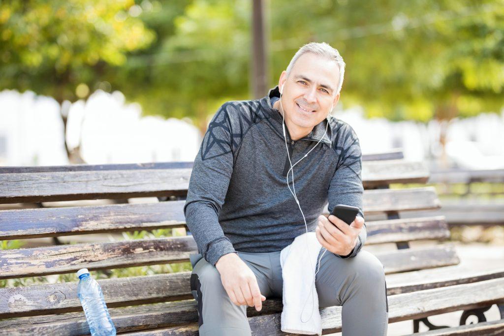 Un hombre maduro y con sonrisa amplia escucha música en el teléfono mientras descansa un poco del ejercicio que está haciendo en el parque