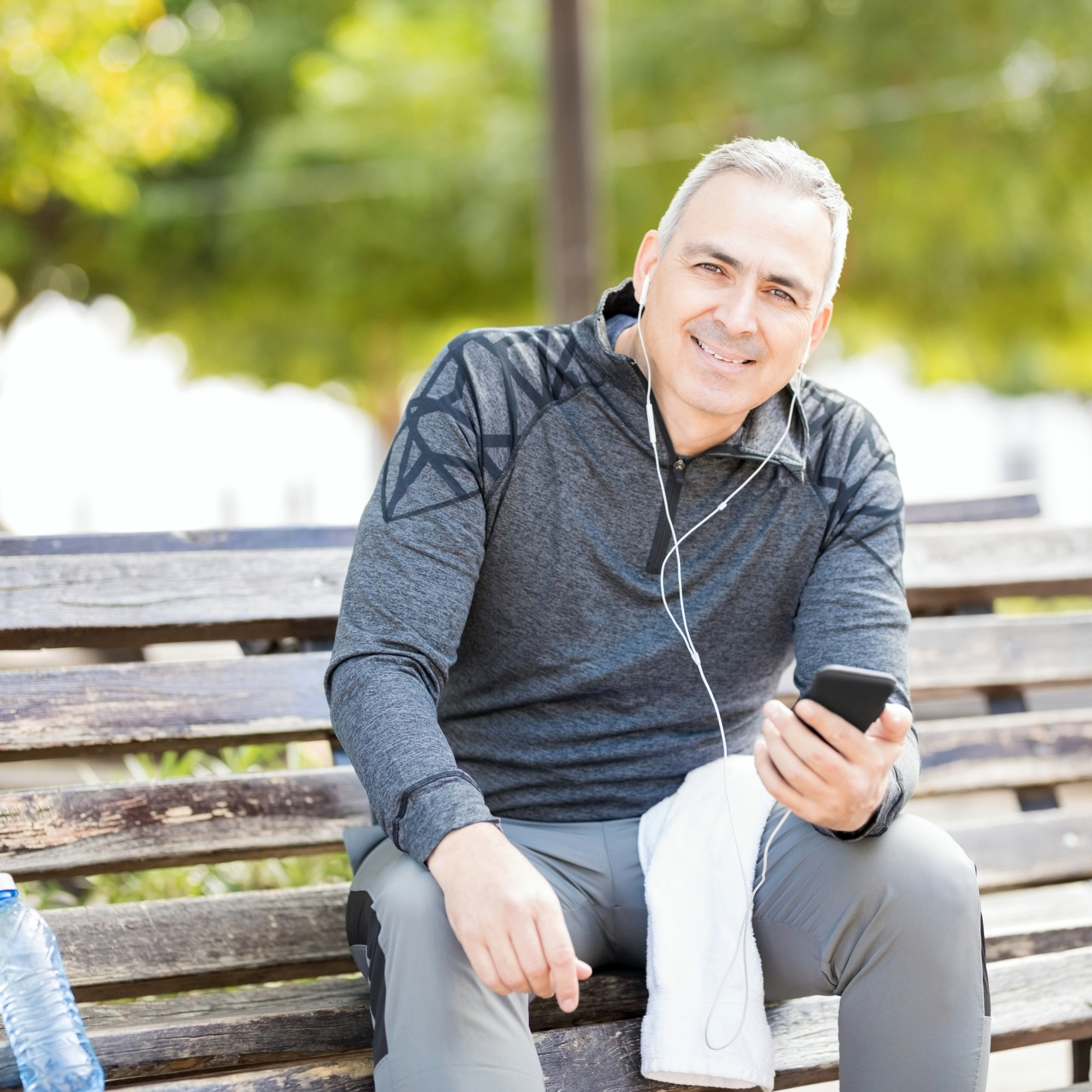 Good looking mature man listening to music with a smartphone while taking a break from exercising outdoors in a park
