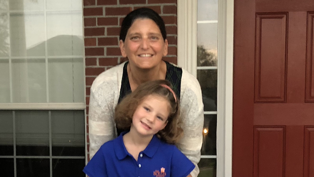 breast cancer patient Stacy Hanson with her daughter outside house by front door