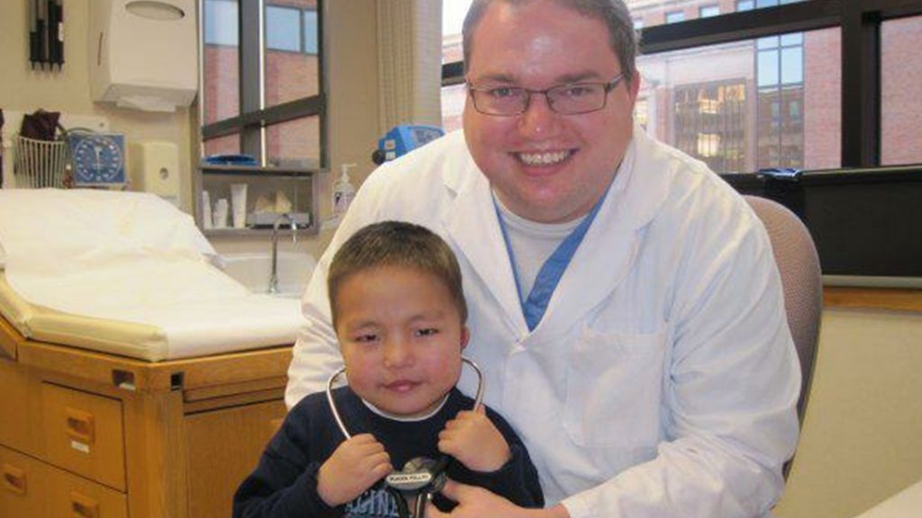 In the Loop patient Dr. Brandon Lane Phillips in his office with a young patient