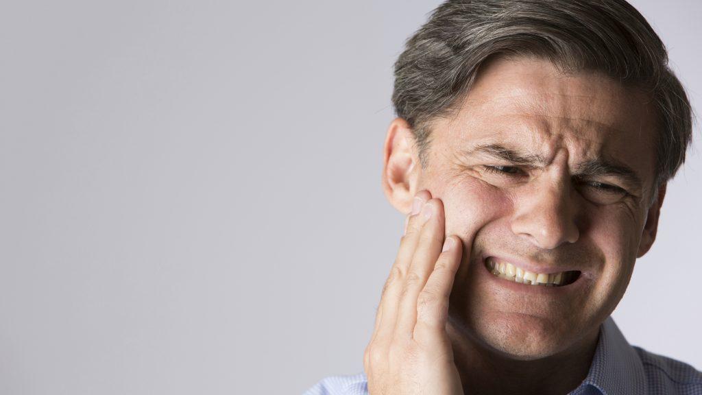 Un hombre con dolor de la mandíbula o de la muela