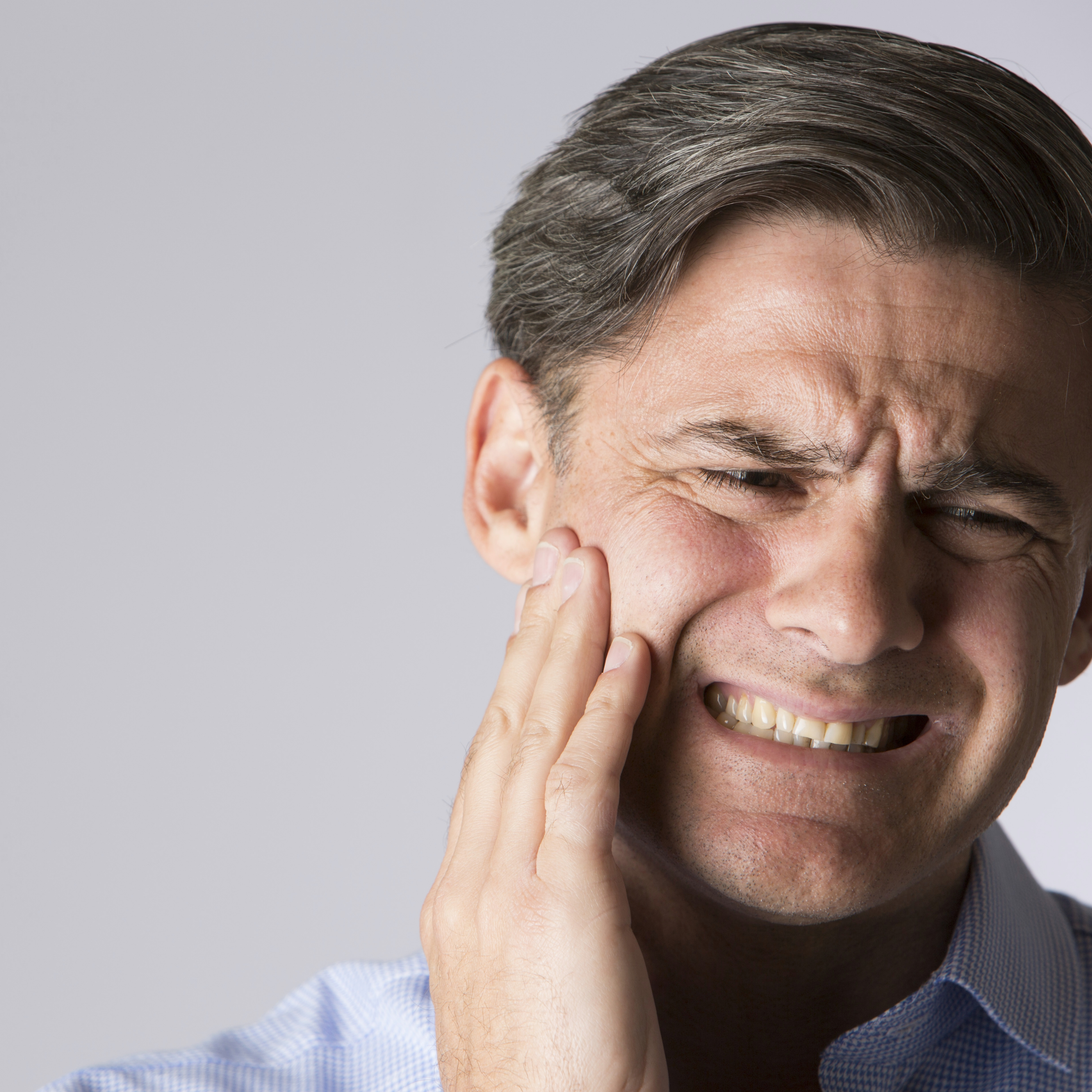 Man suffering with jaw pain or toothache