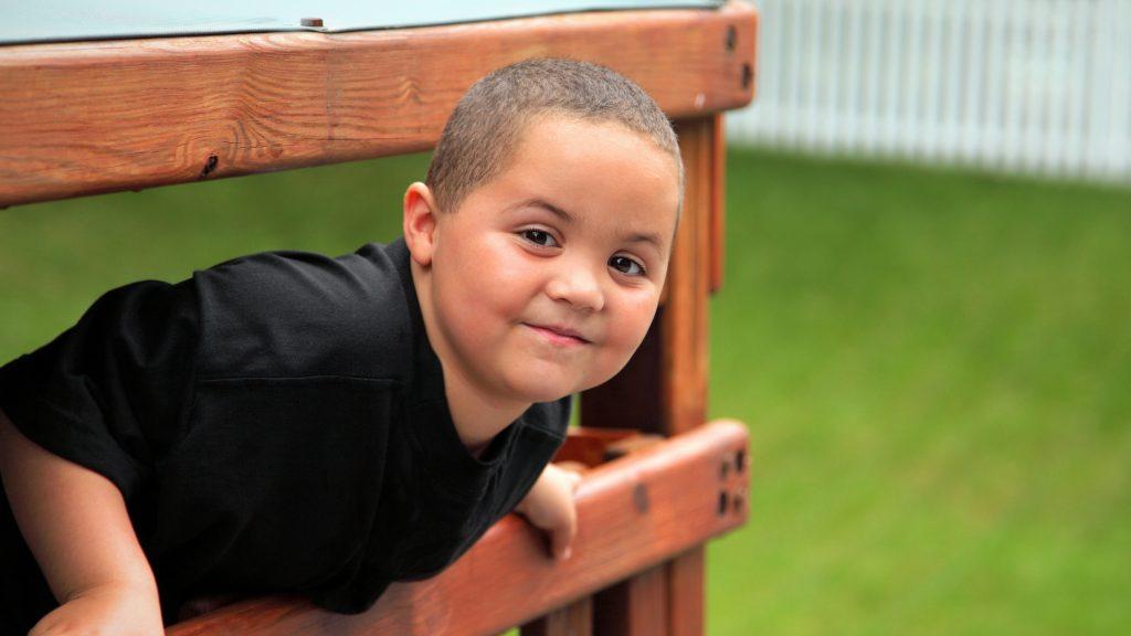 Un niño sonriente juega afuera