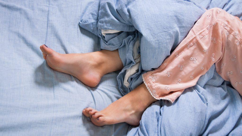Foto de unas piernas femeninas enredadas en las sábanas y las cobijas de la cama