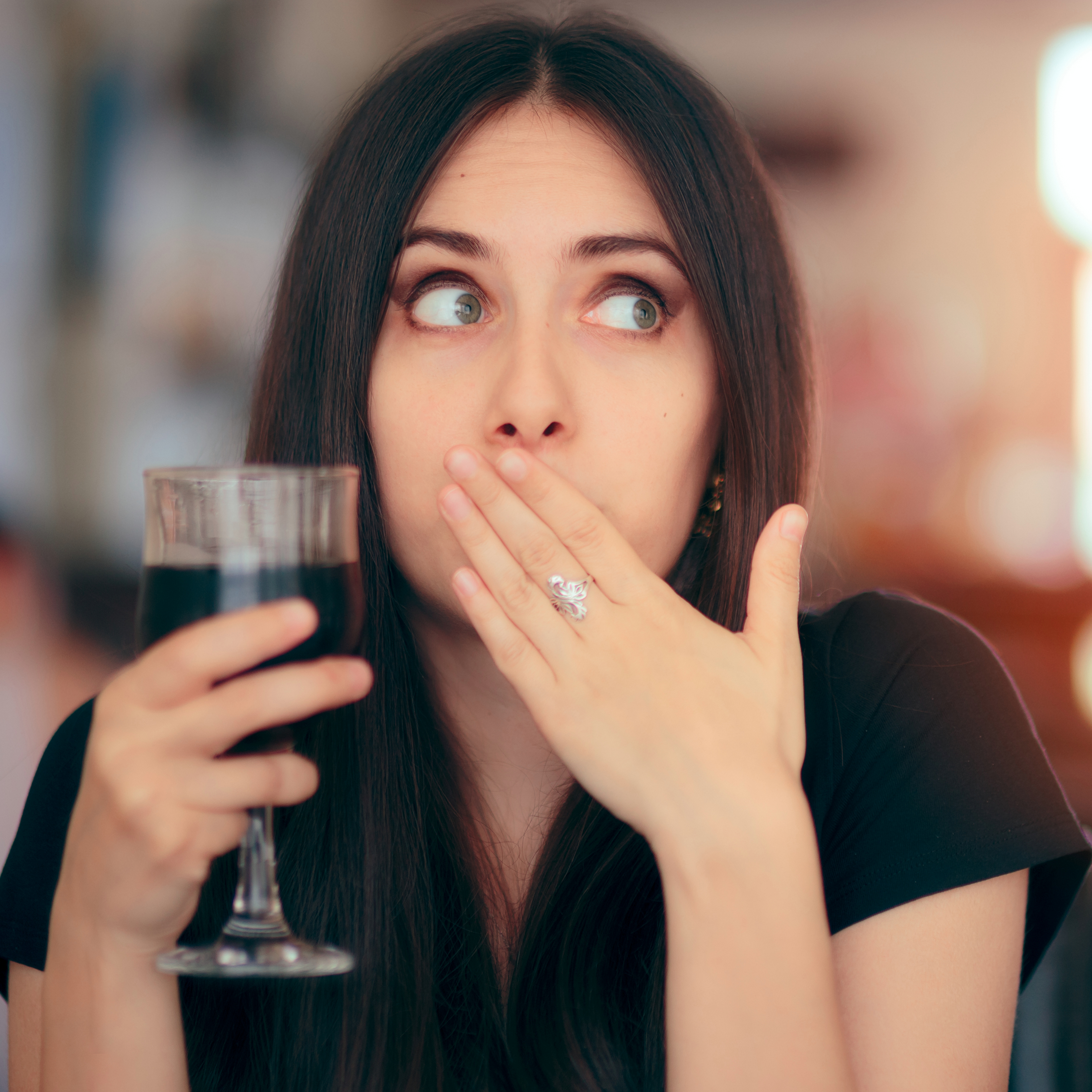 a woman holding a glass with soda or wine and covering her mouth because she's burping or hiccuping, maybe feeling sick
