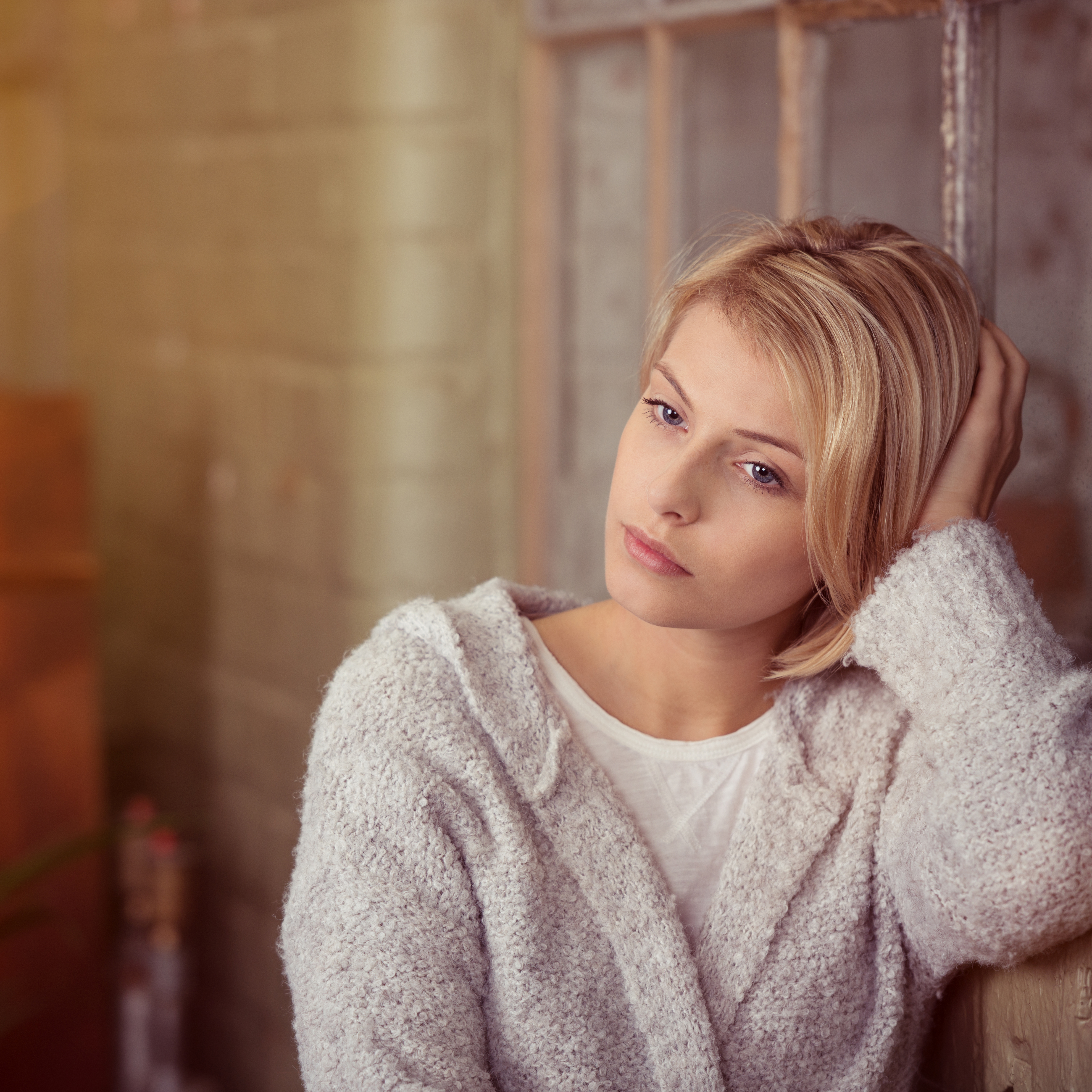 a young woman leaning against a brick wall and window sill, looking serious or sad