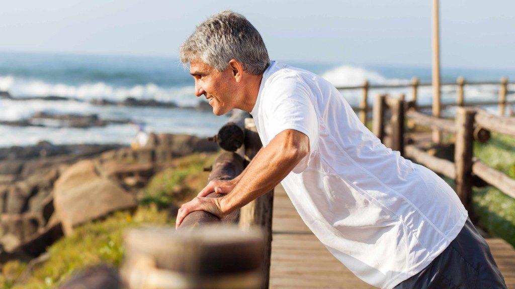 Un hombre de mediana edad hace ejercicio y se estira cerca del mar