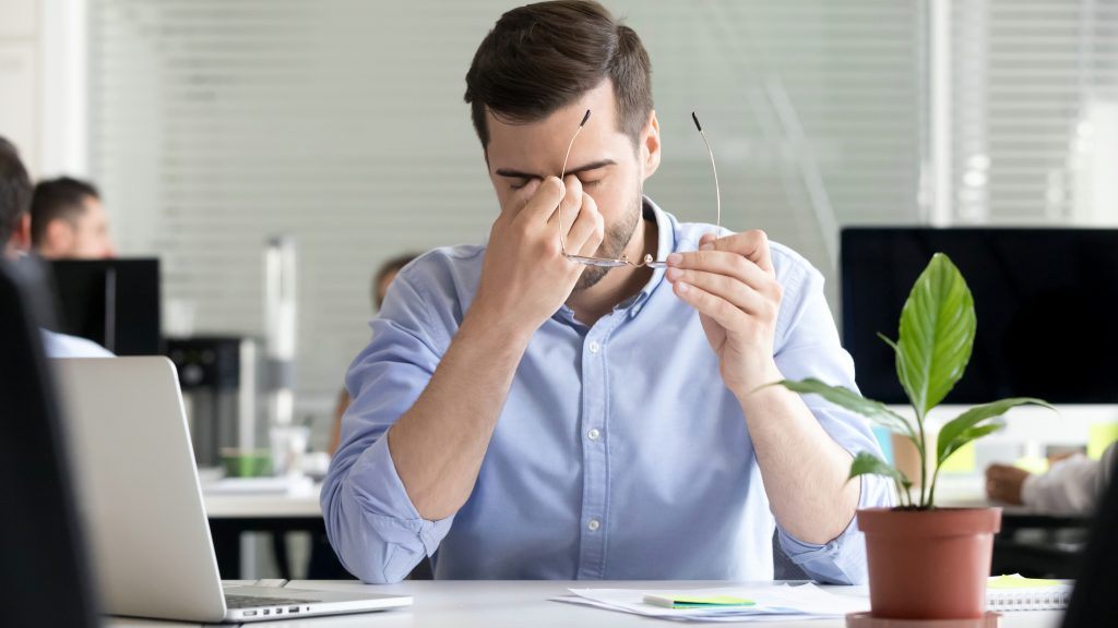 a young man rubbing his tired, strained, irritated eyes while working at a computer in his office