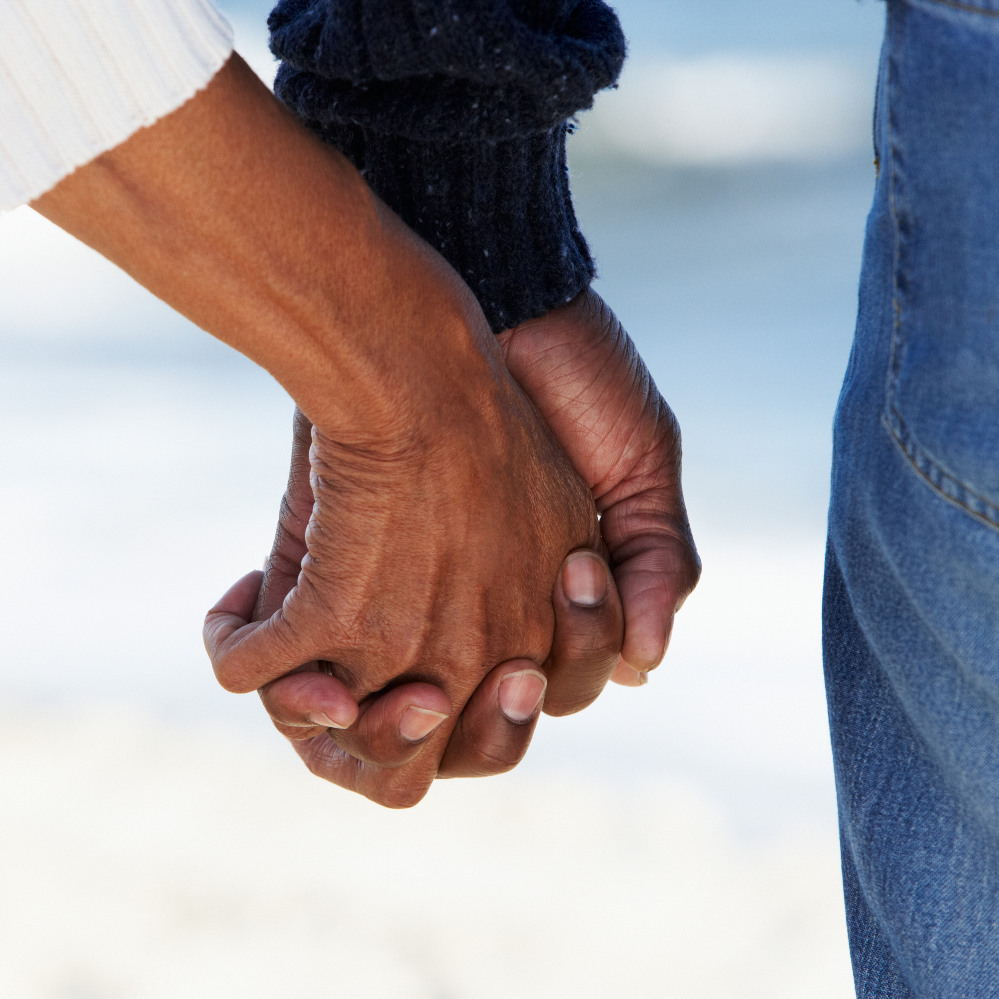 closeup of couple holding hands on the beach