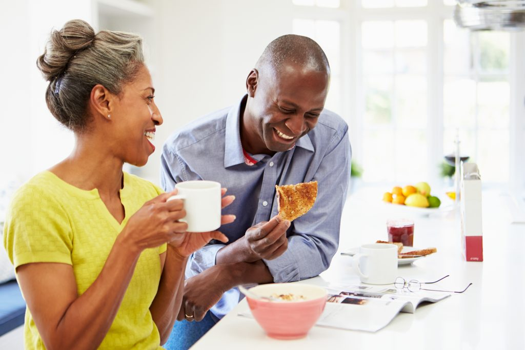 a middle-aged woman and man laughing and eating together in the kitchen