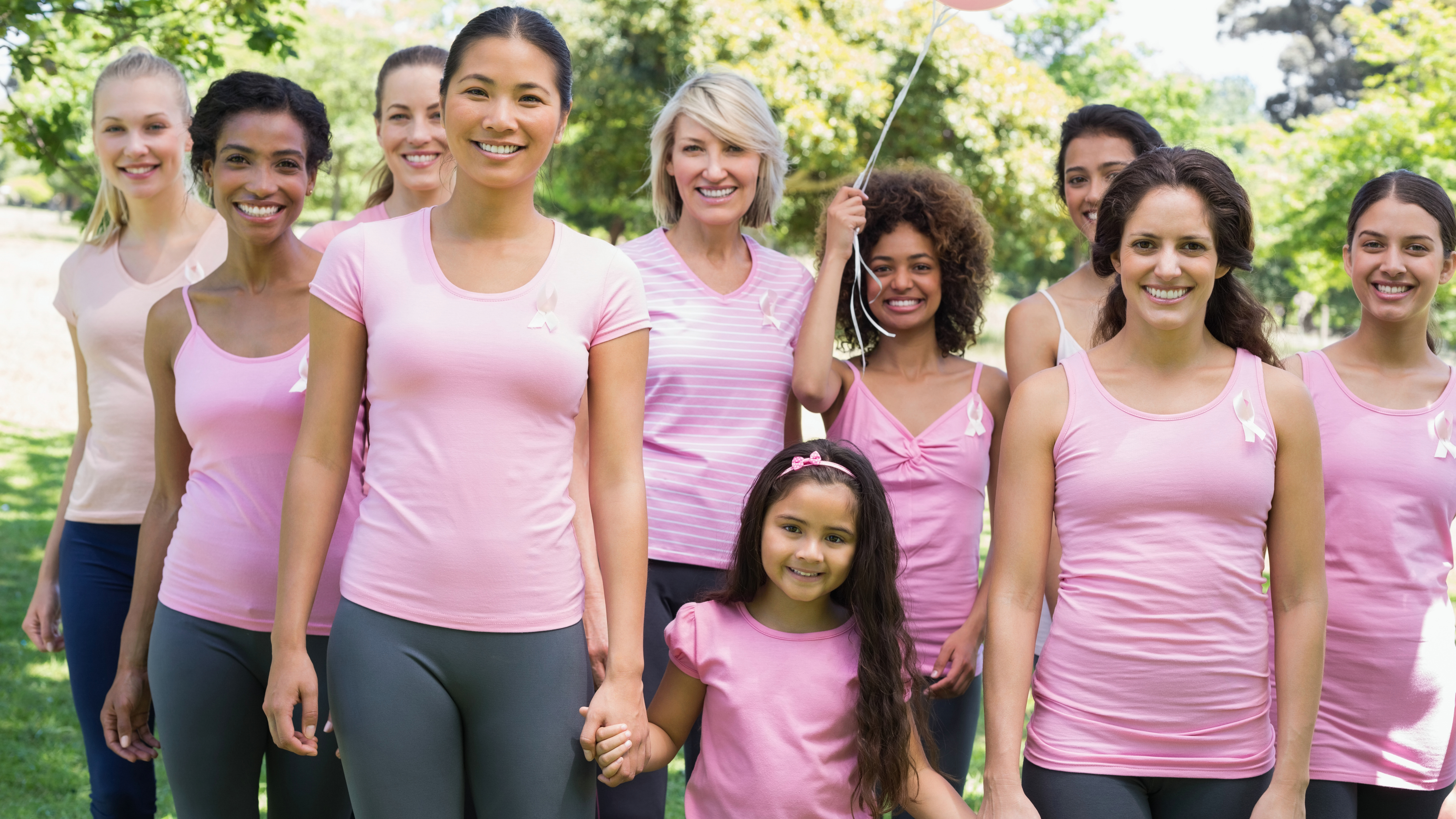 a group of multiethnic women and a young girl standing outside in a park, all wearing pink and supporting breast cancer awareness