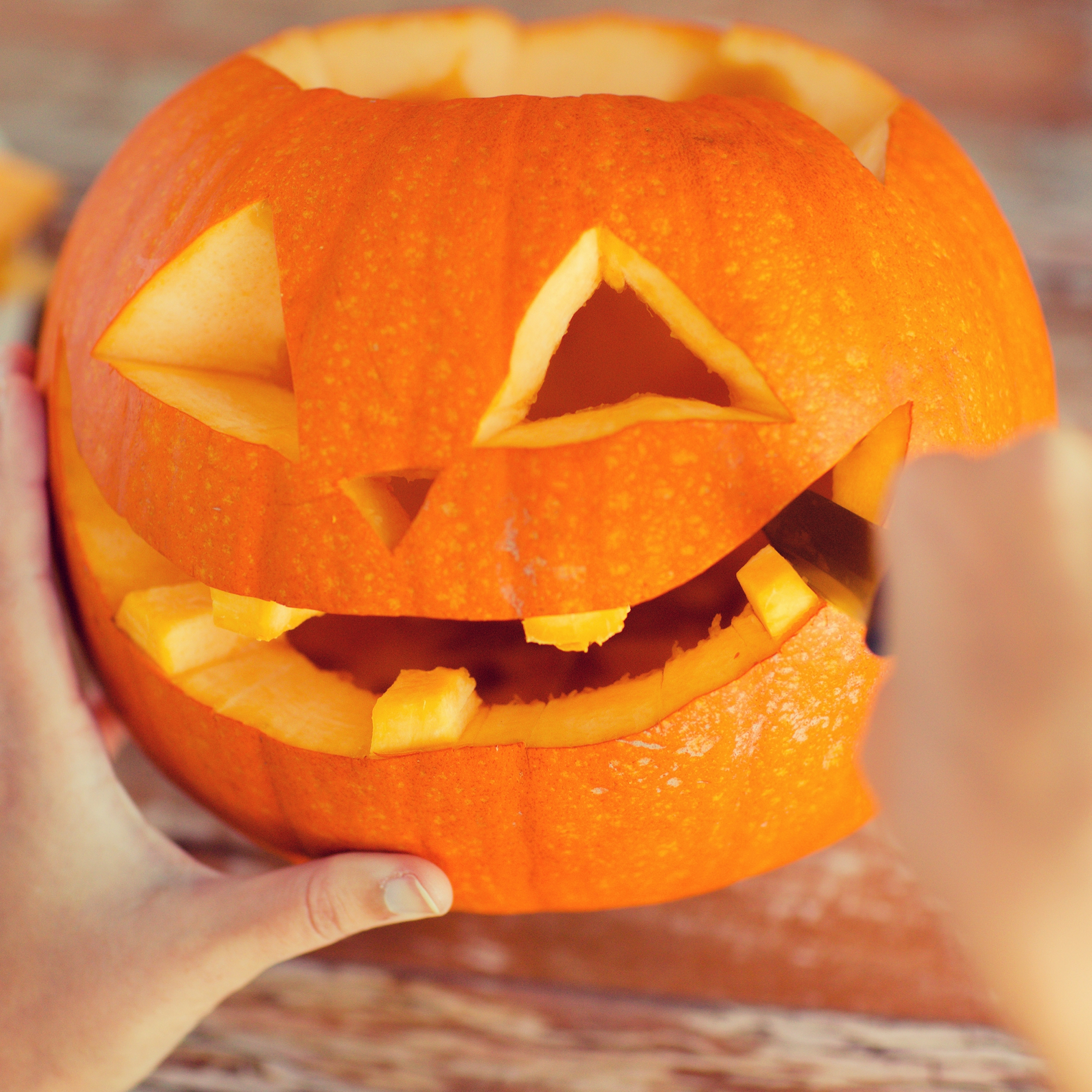 a person carving a Halloween pumpkin with a knife