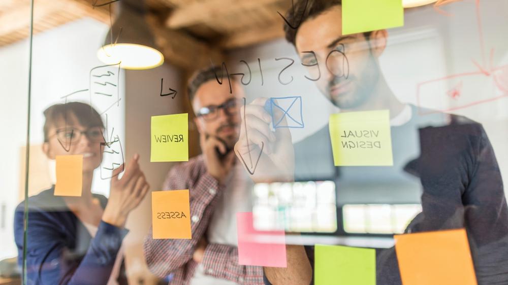 La gente de negocios se reúne en la oficina y usa notas de post it para compartir ideas. Concepto de lluvia de ideas. Nota adhesiva en la pared de cristal.