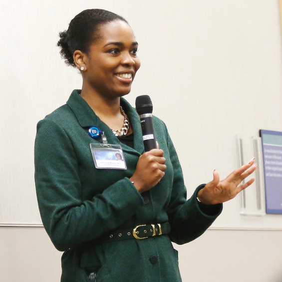Dr. LaPrincess Brewer holding a microphone and addressing an audience