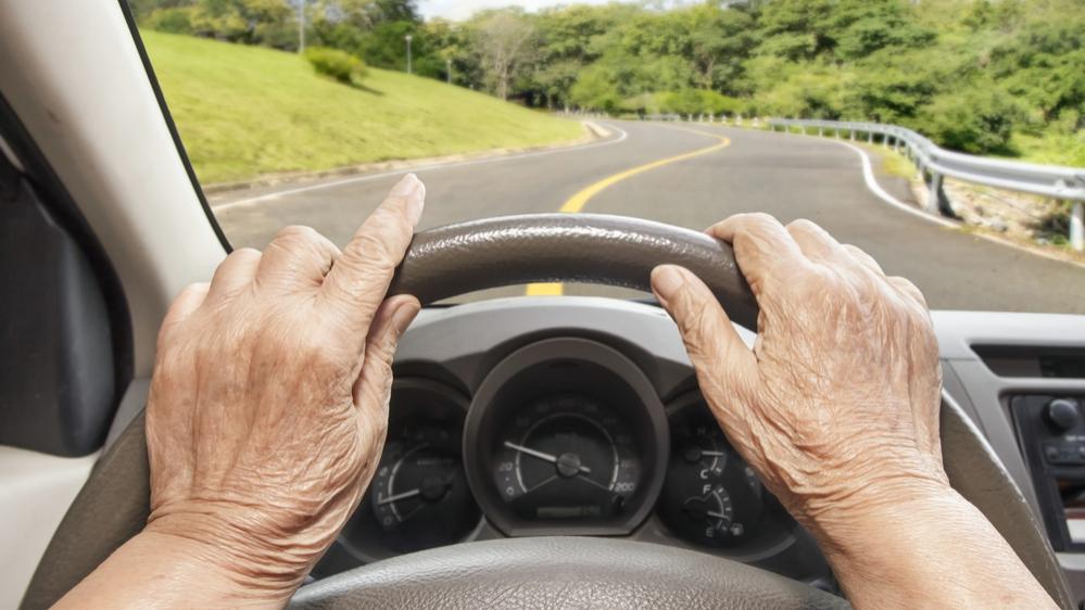 Imagen del volante y de las manos de una persona anciana que conduce un vehículo lentamente por la carretera
