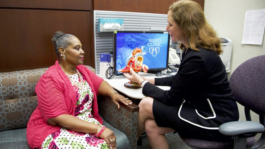 a female cardiologist talking with a woman patient in an exam room about heart disease using a model of a heart