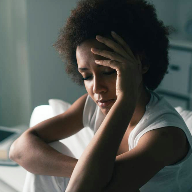 a young woman sitting in bed in a dark room, with her eyes closed tying to sleep holding her hand on her forehead, perhaps suffering from insomnia, sadness, depression or stress