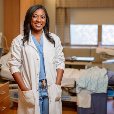 Dr. Kayla Nixon in scrubs and a white jacket smiling in a patient hospital room