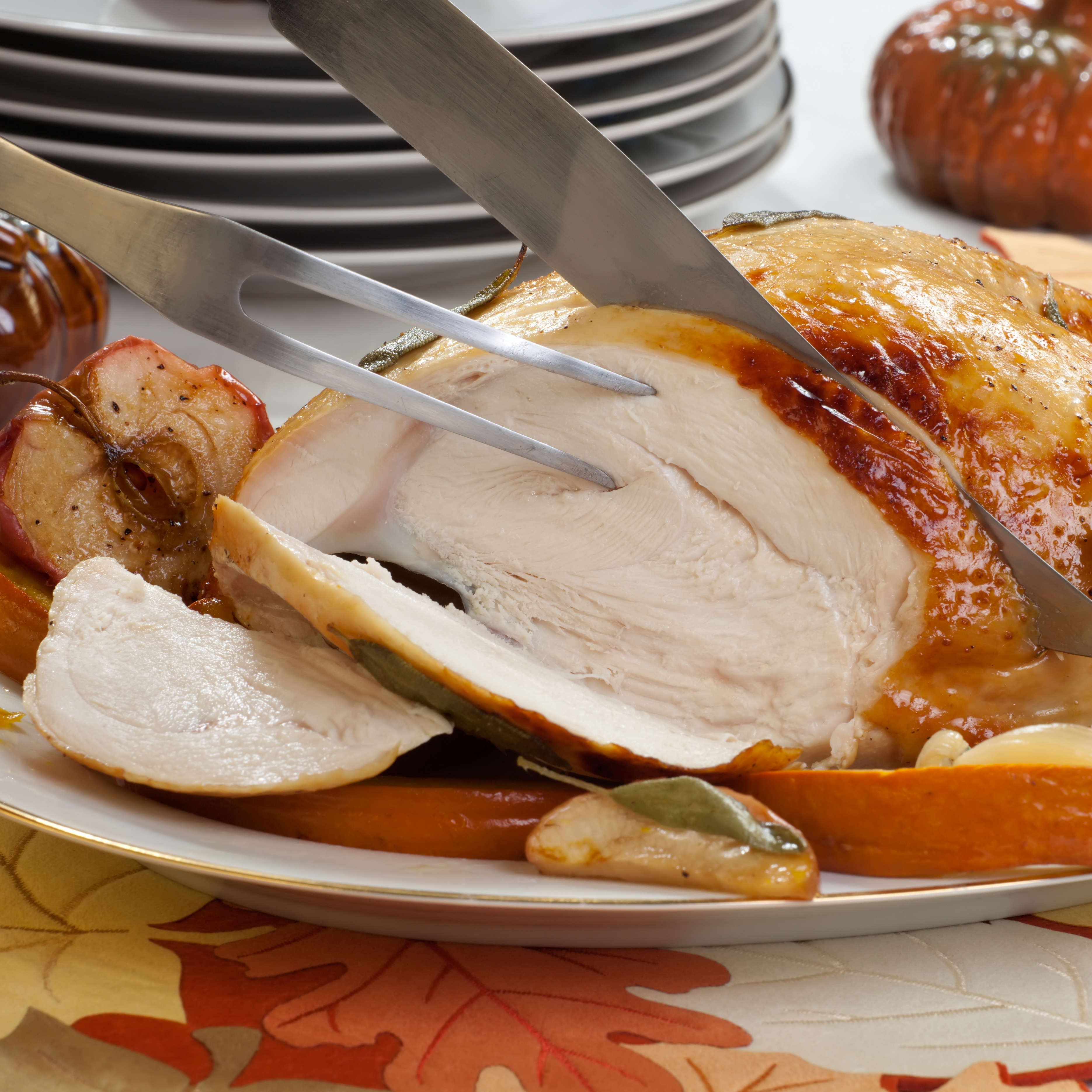 Carving sage - honey butter rub turkey breast garnished with roasted pumpkin and apples in fall themed surrounding