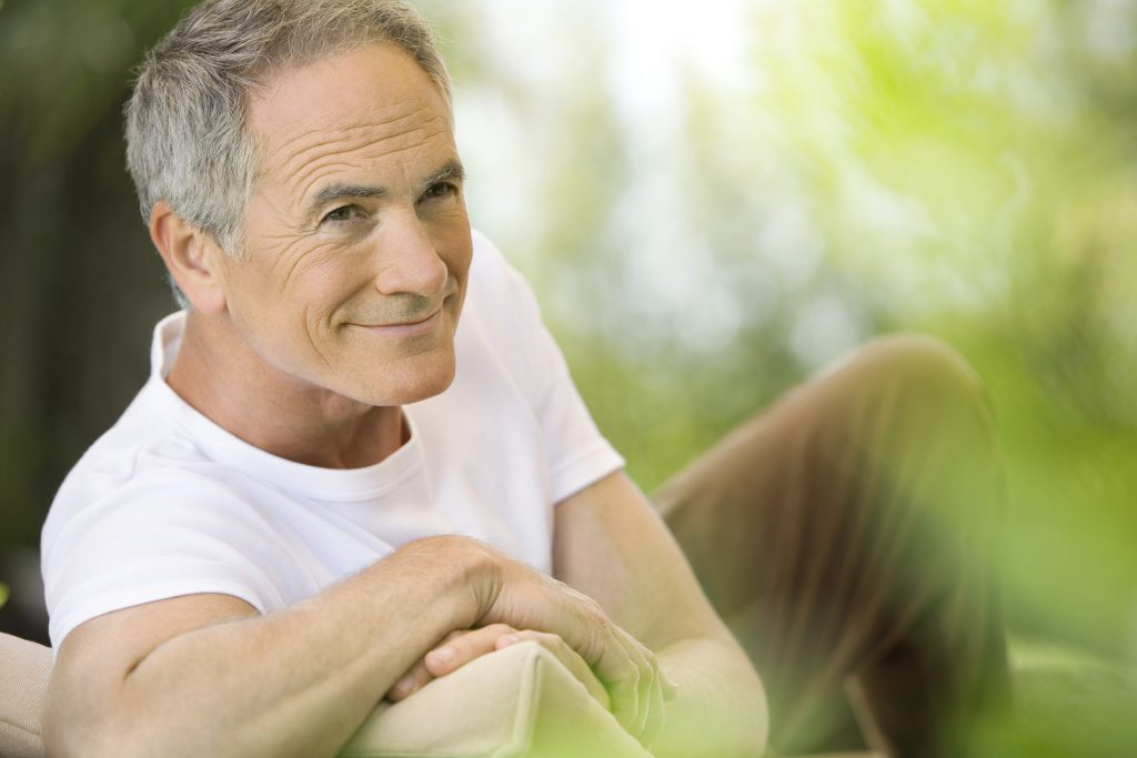 a smiling middle-aged man, sitting on a bench outside