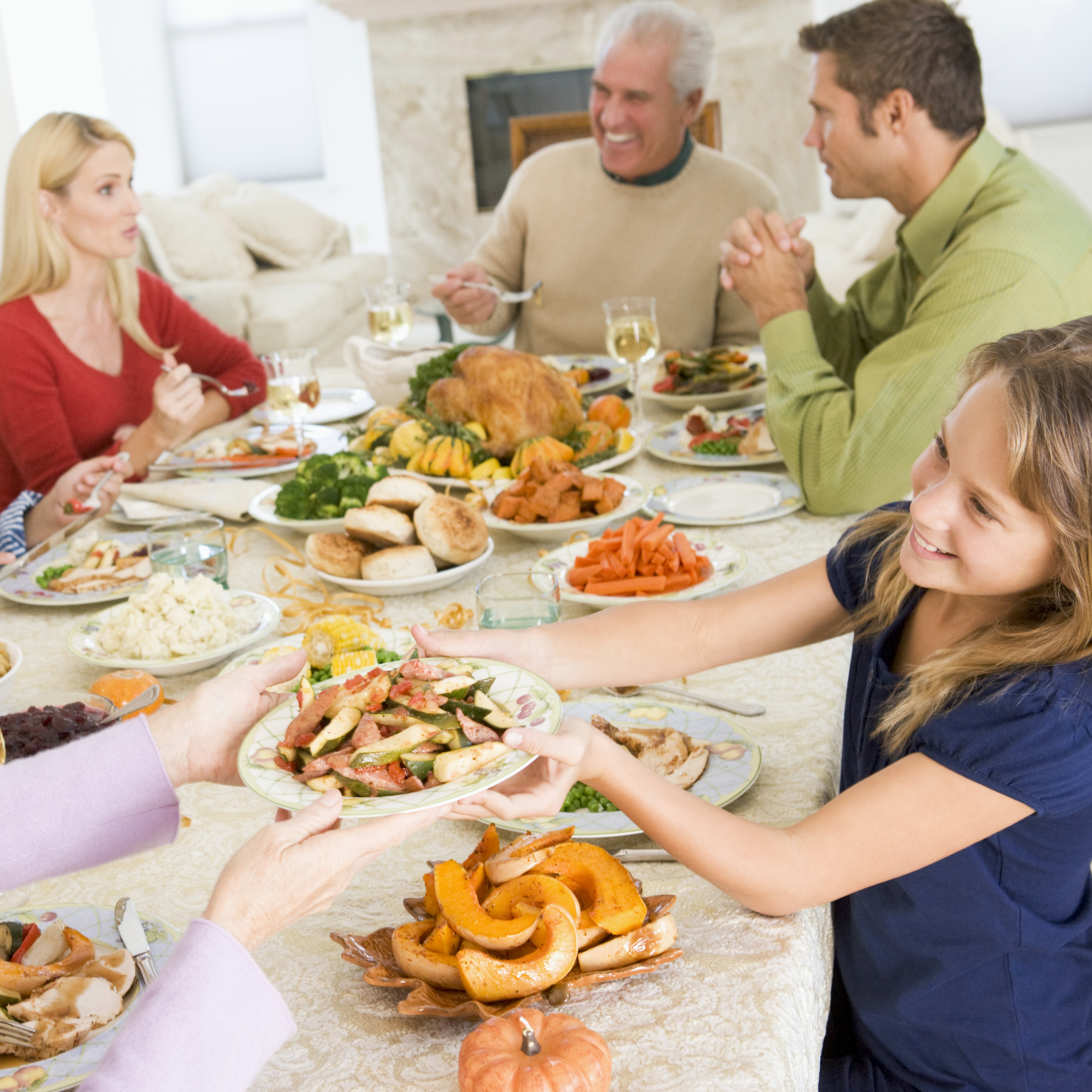 a family, a group of adults and children gathered around a festive holiday dinner table with a turkey in the middle of the table