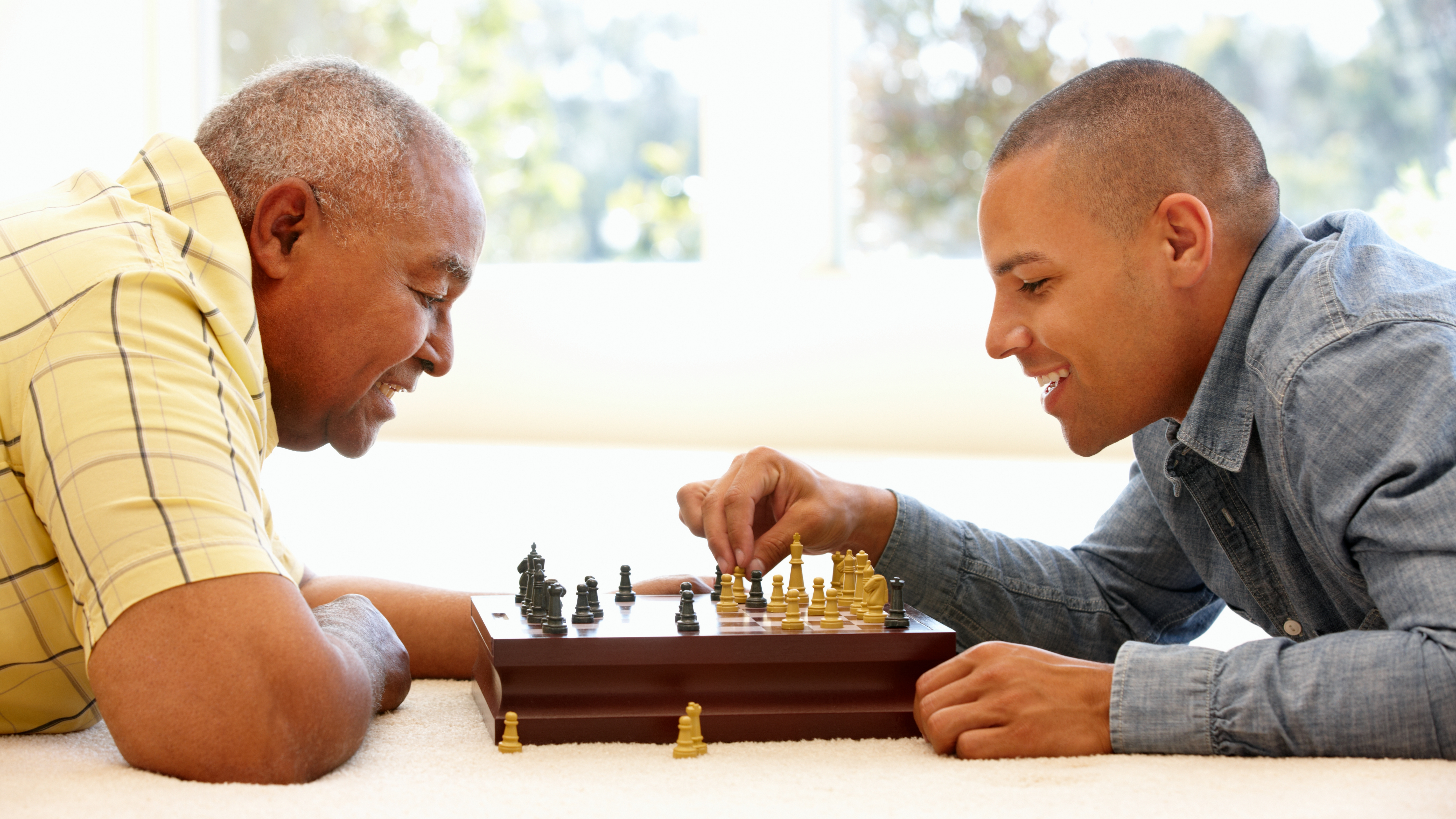 sitting by a window and smiling, an older man having fun and playing the game of chess with a younger man